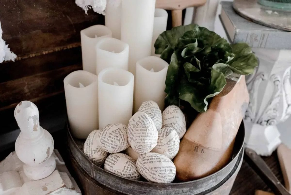 in a basket are white church cndles, green foliage and a pile of egg shapes covered in pages from old books