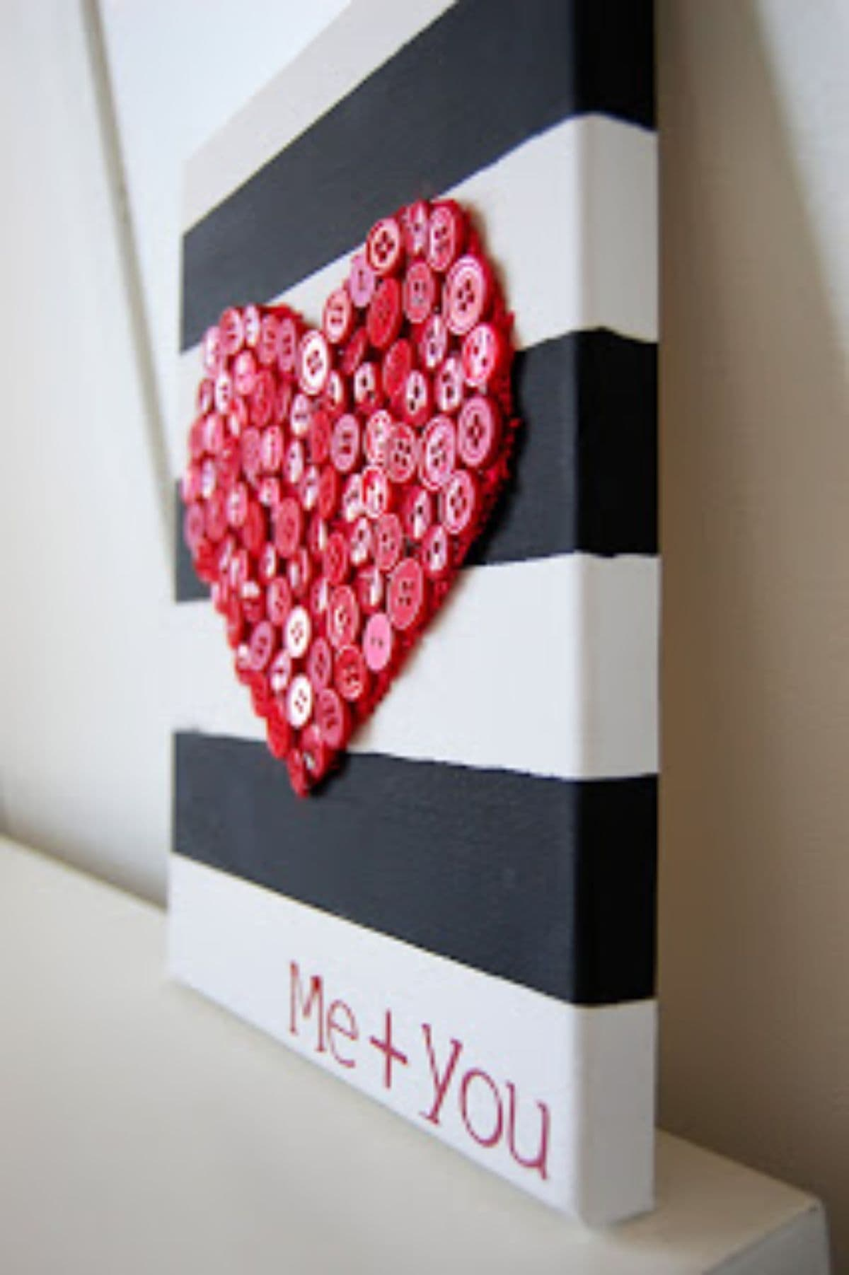 "a side-on image of a blacj and white striped square hanging from a wall. On the front of the square is a heart shape made of red buttons. Underneath is the red text ""ME + YOU"""