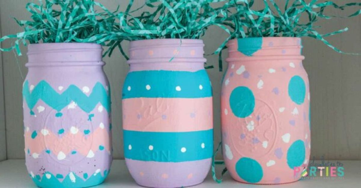3 mason jars are decorated in pink, blue and white. The tops are stuffed with green shredded paper