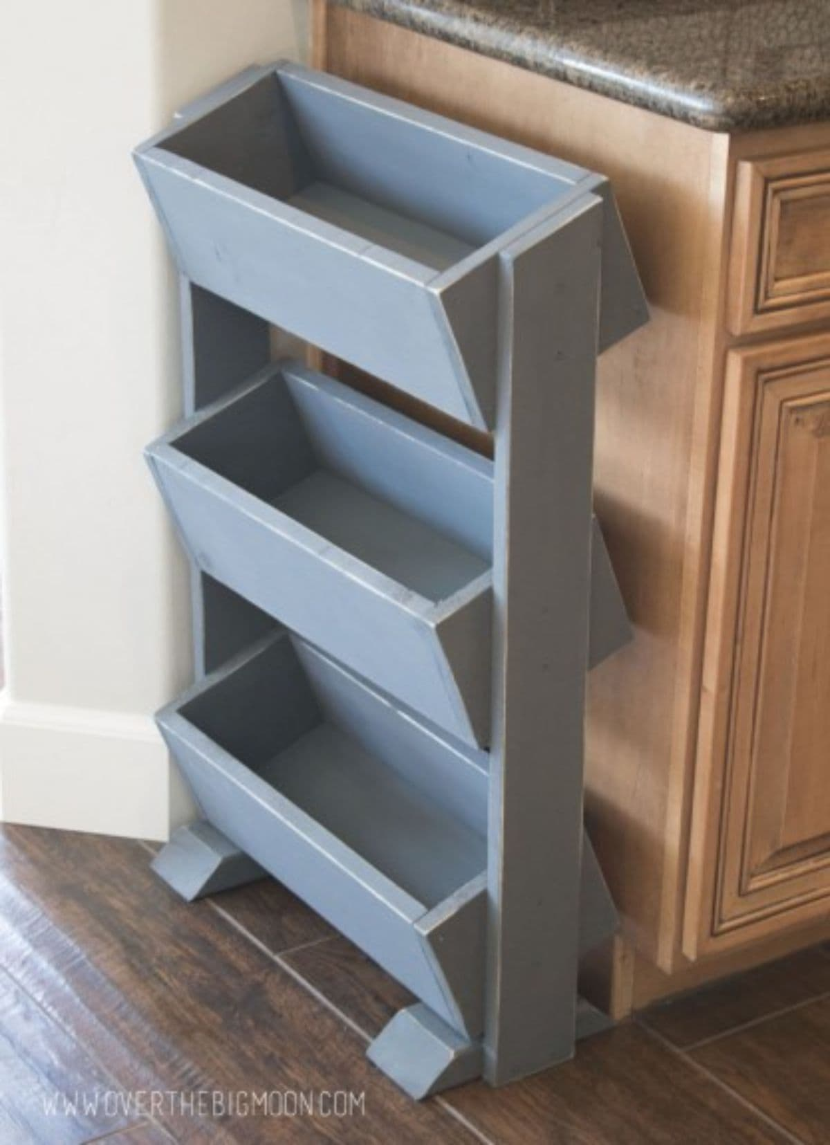 Sitting on the edge of a kitchen unit is a 3 tier vegetable display unti, with each grey wooden box shelf at a slant