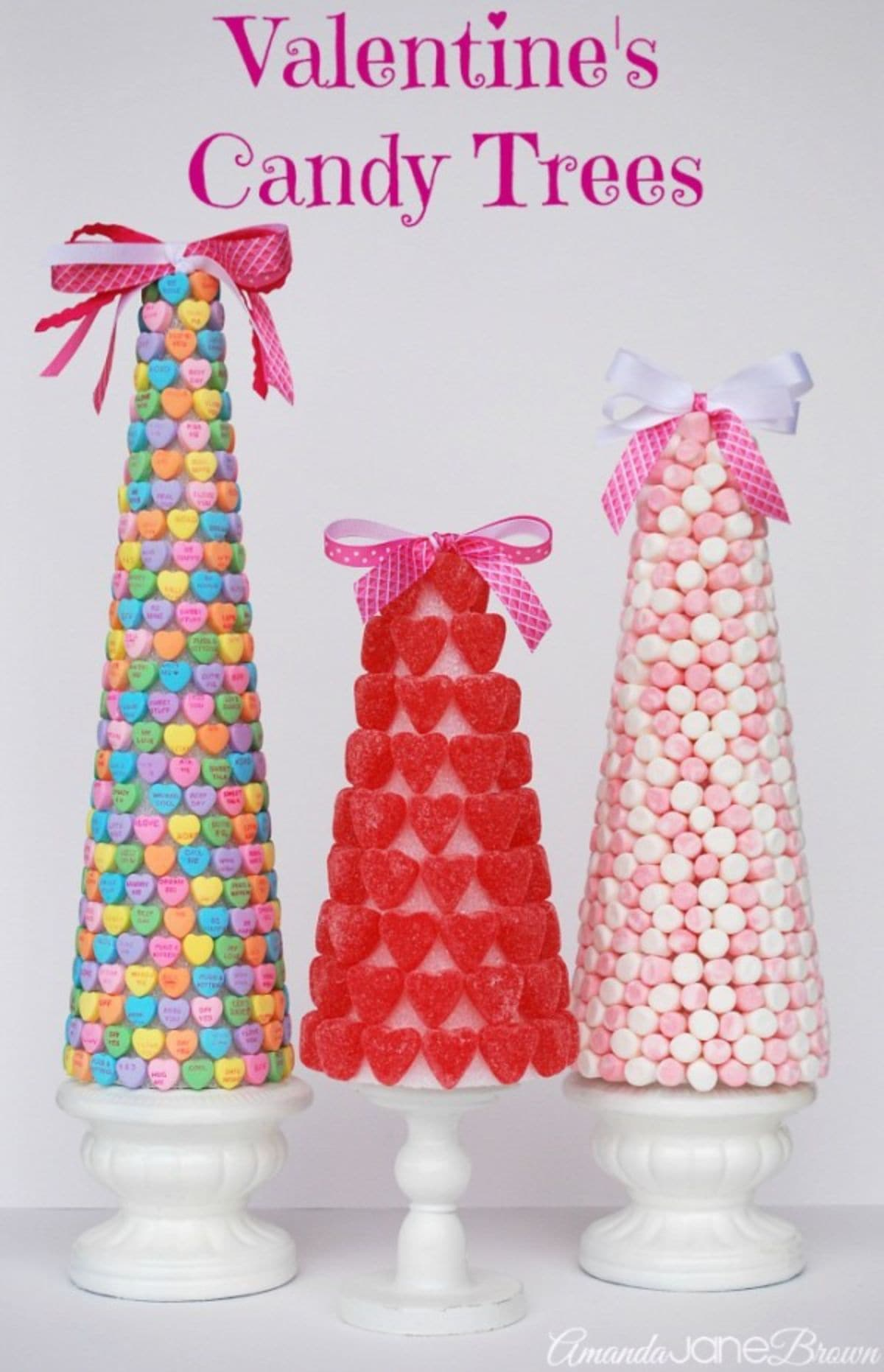 Three cones of varying sizes sit next to each other. On the left is a cone covered in candy hearts, in the middle a cone covered with jelly hearts, on the right a cone covered in sugar balls