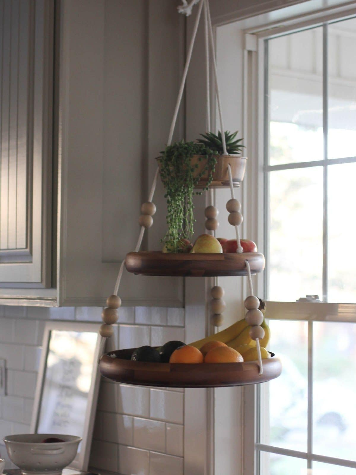 Hanging in front of a window is a 3 tier hanging shelf with fruit on each level