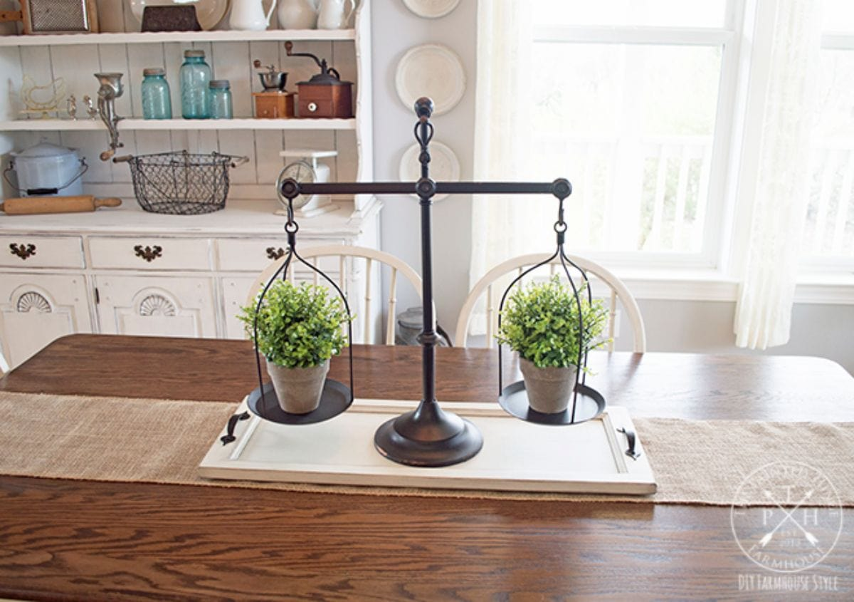 On a kitchen table is a white wooden tray. On top of it are some old weighing scales with a plant pot balanced on each side