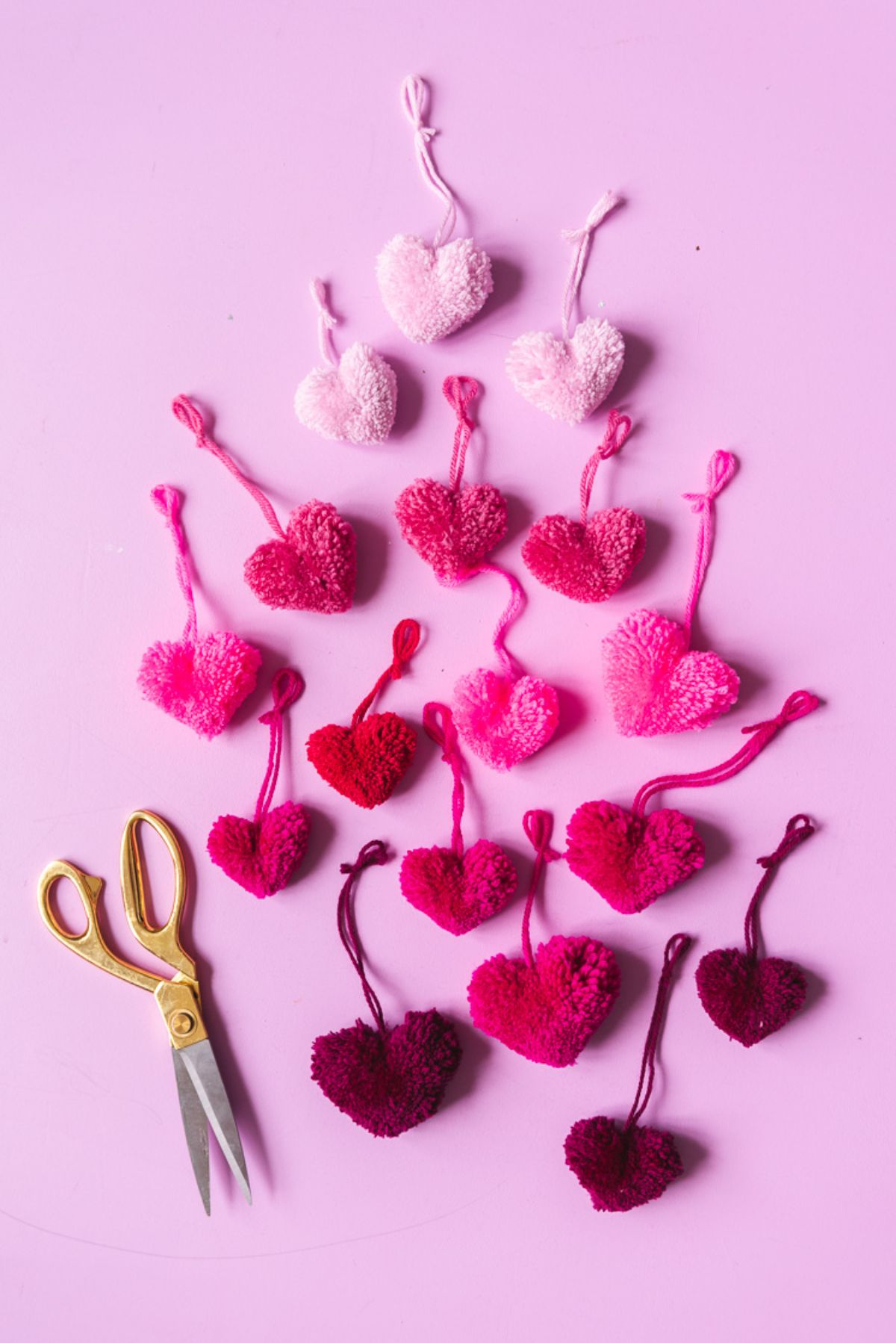 on a pink background are 16 knitted hearts graded from light pink to dark red. On the left is a pari of yellow handled scissors