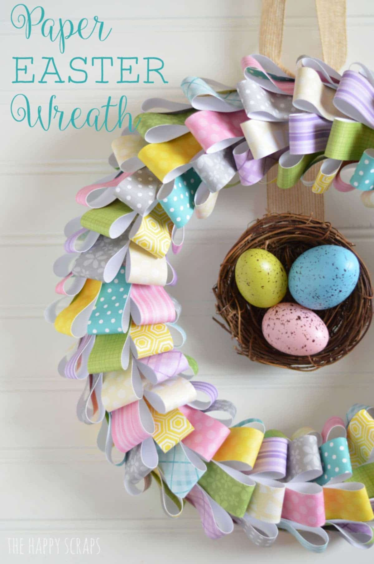 on a white background a wreath made of folded colored paper surrounds a twig basket with chocolate eggs inside