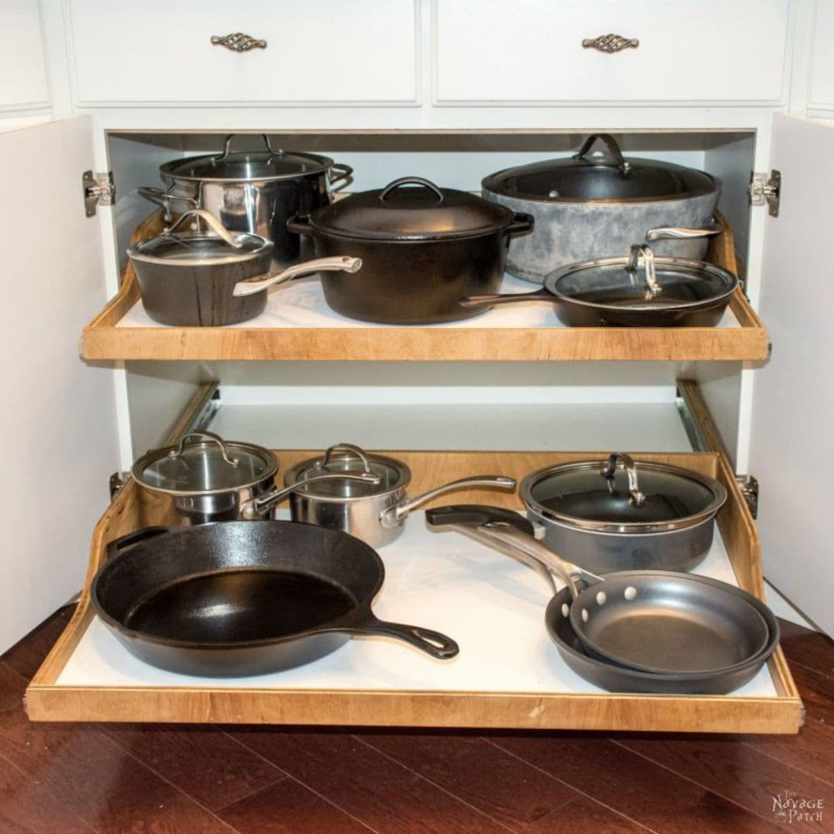 The inside of a kitchen cabinet is shown with 2 sliding shelves slightly oulled out. Each shelf holds pots and pans