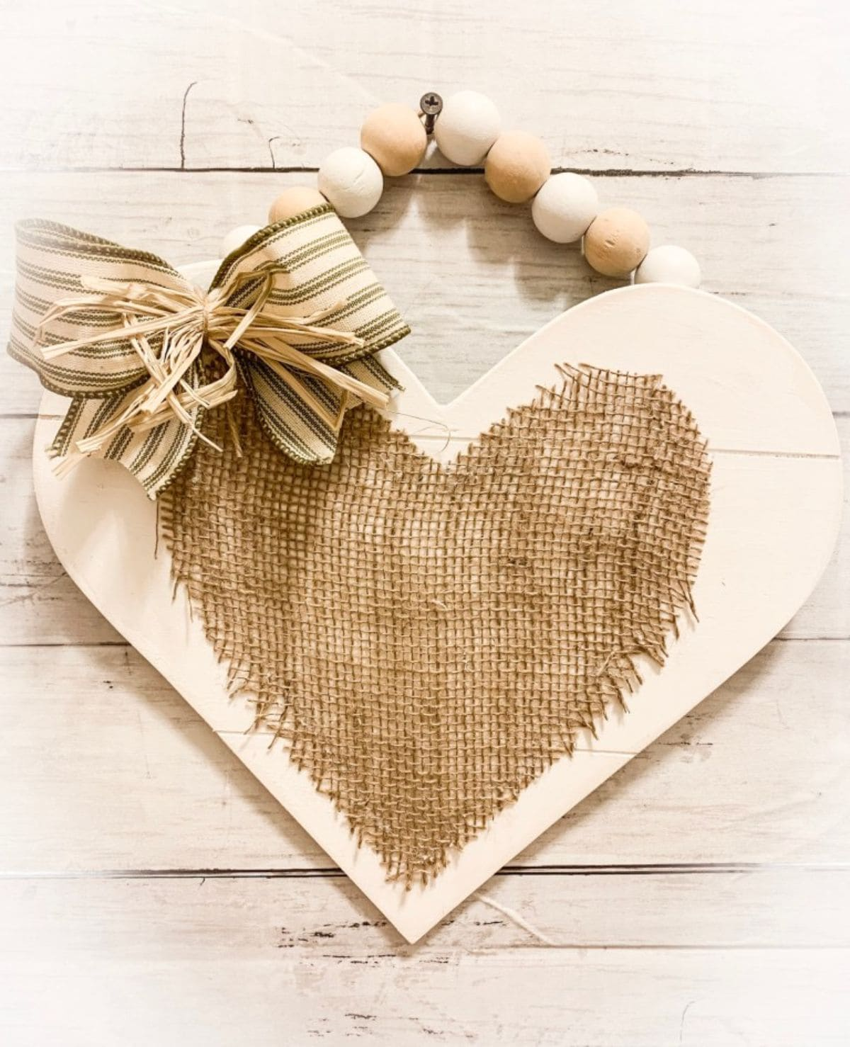 Hanging on a cream brick wall from a strong of wooden balls is a cream heart with a burlap heart stuck to the front.