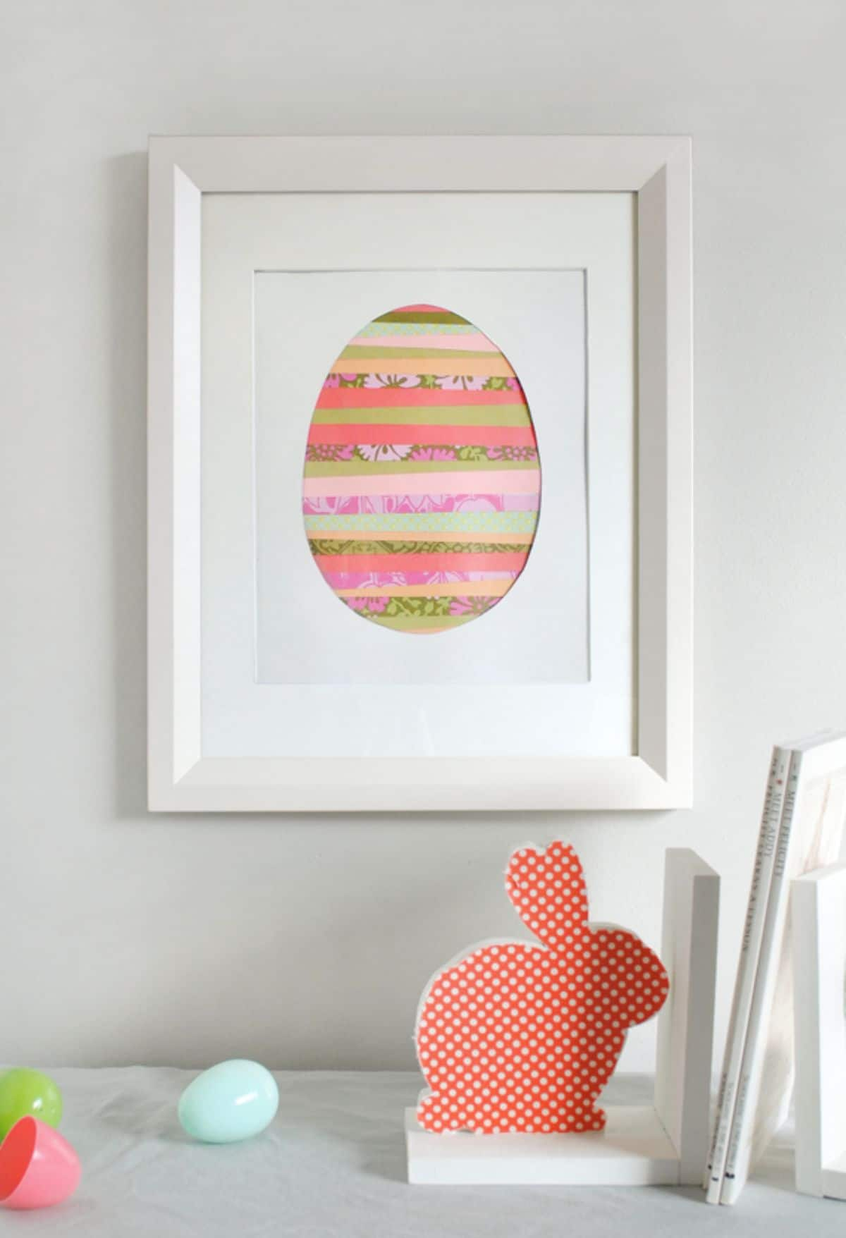 Hanging on a wall is a framed picture of a striped egg. In front sits a red bunny cutout