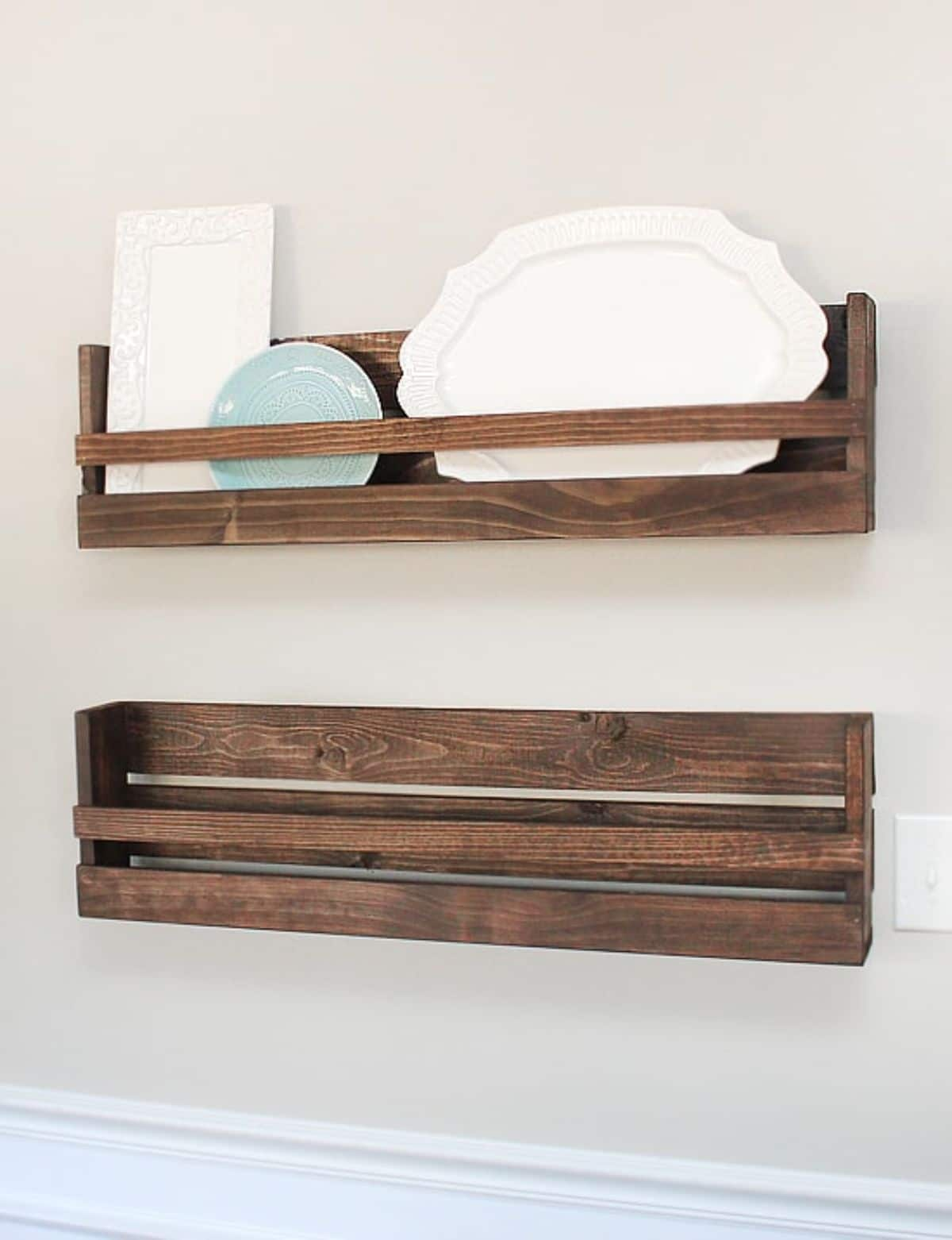 On a cream wall are 2 dark wooden spice racks. In the top rack are some different sized plates