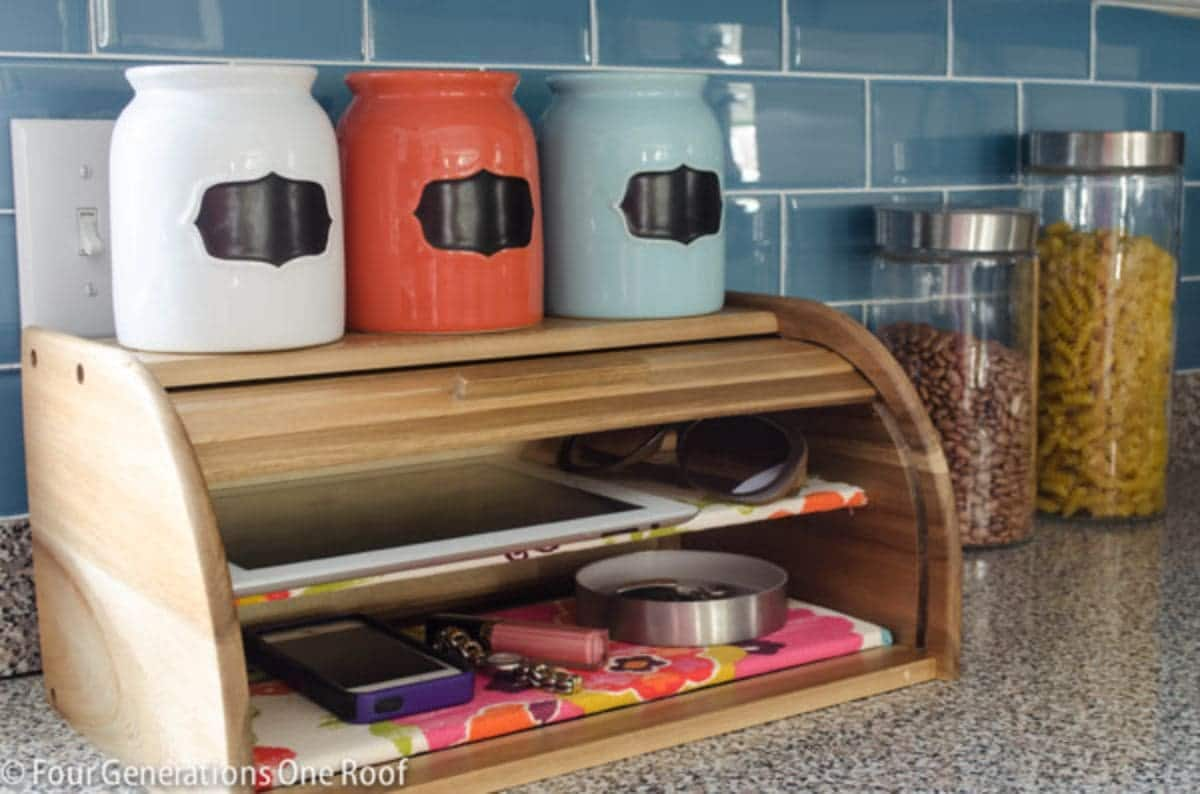 ON a countertop with blue subway tiles behind it is a wooden bread bin. On top sit 3 painted jars in white, orange and blue. A shelf has been put in the bread bin half way up and an ipad sits on teh top shelf with phones on the bottom