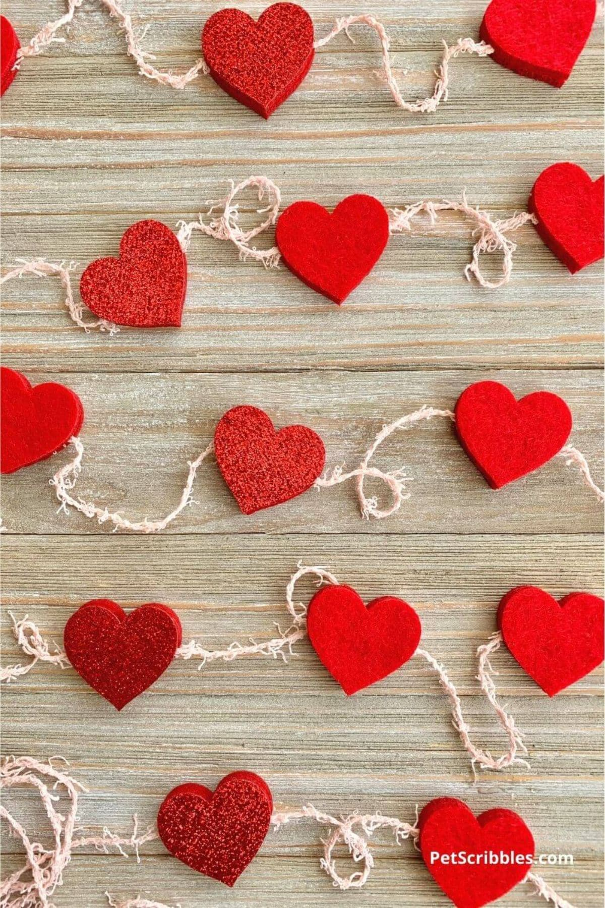 On a wooden background are 3 strongs of red felt hearts