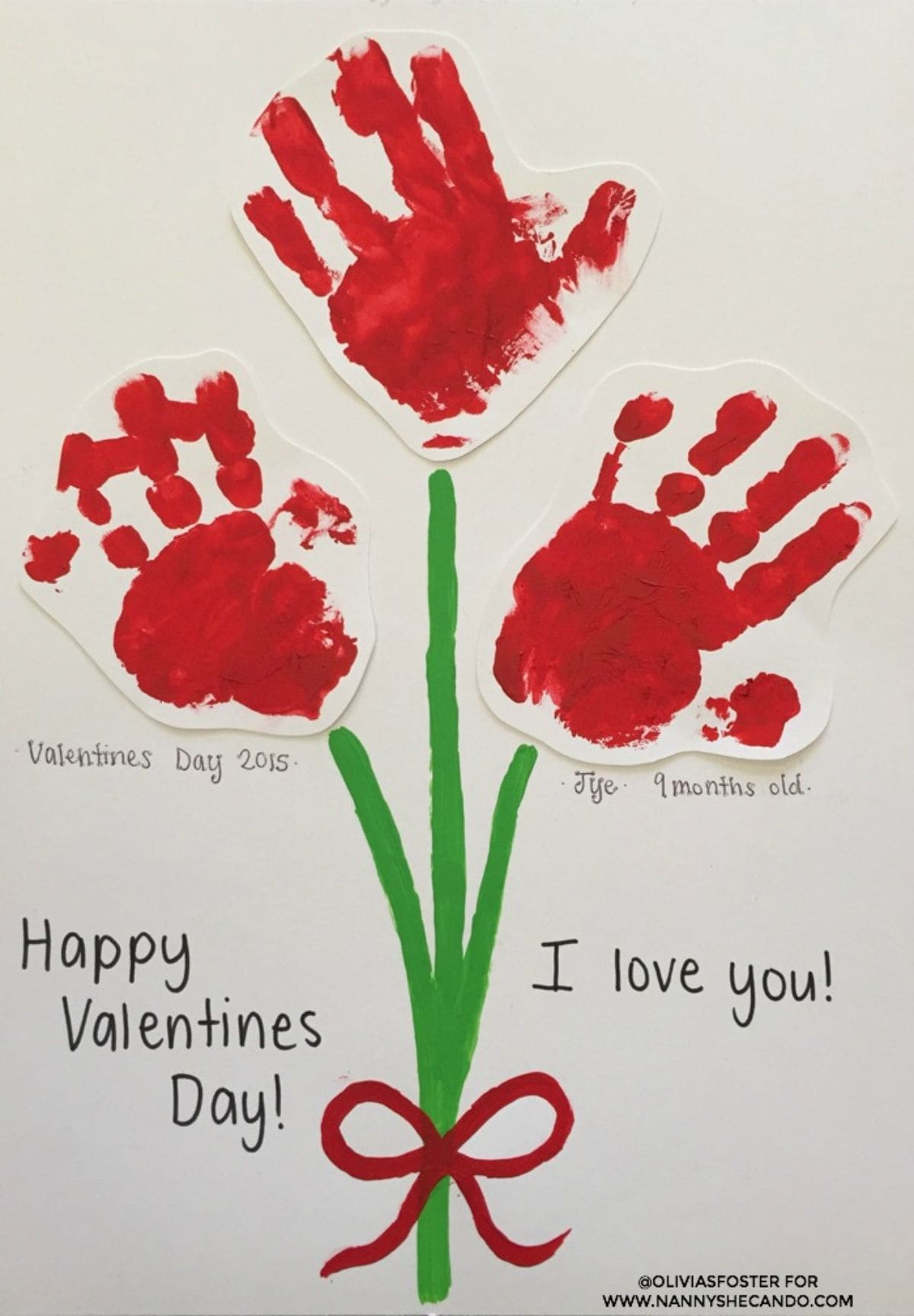 "A child's drawing of a bunch of flowers made up of green painted stems with a red painted bow, and 3 red handprints as flowers. The text reads ""Happy Valentine's Day! I love you"". Under the left hadn print is ""Valentines Dat 2015"" under the right hand print is ""Tye. 9 months old"""