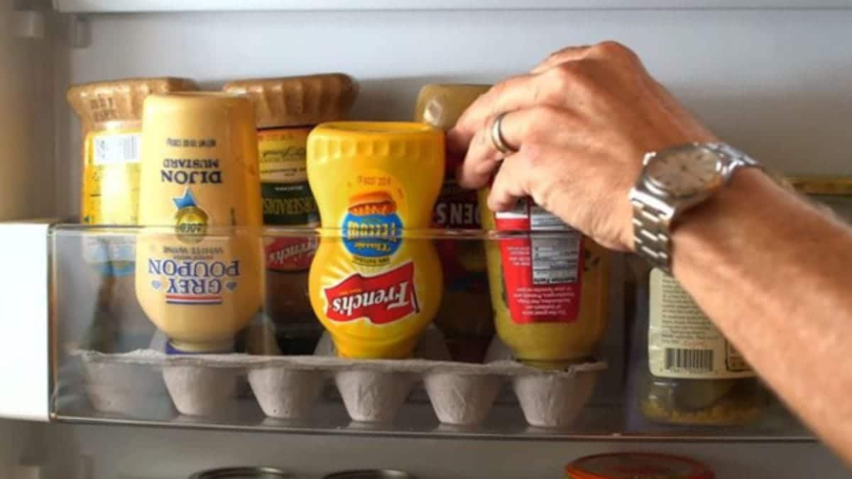 Inside a fridge shelf is the bottom half of an egg box. Upiside down in the egg box are different condiments