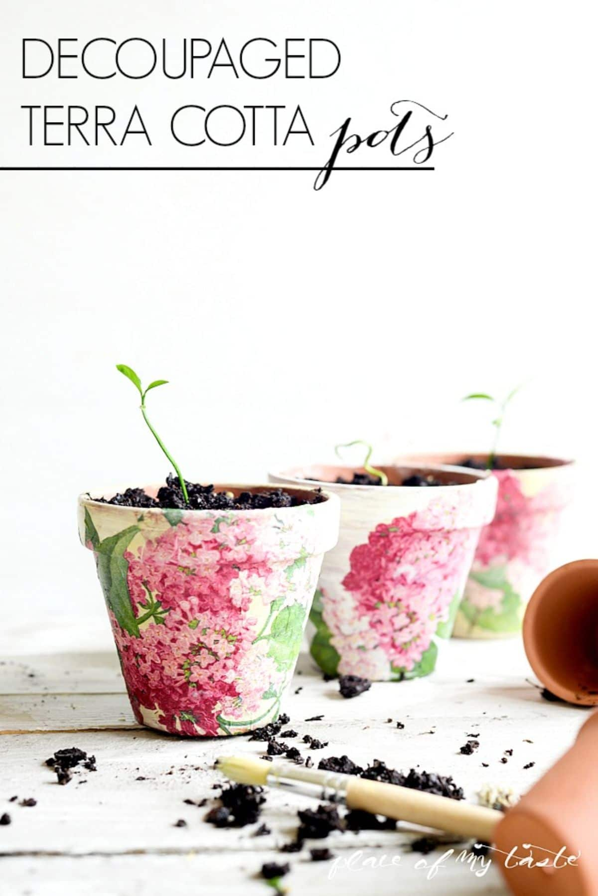 3 plant pots filled with soil have flowers decoupaged around the outside. In the foreground is a trowel with soil on it