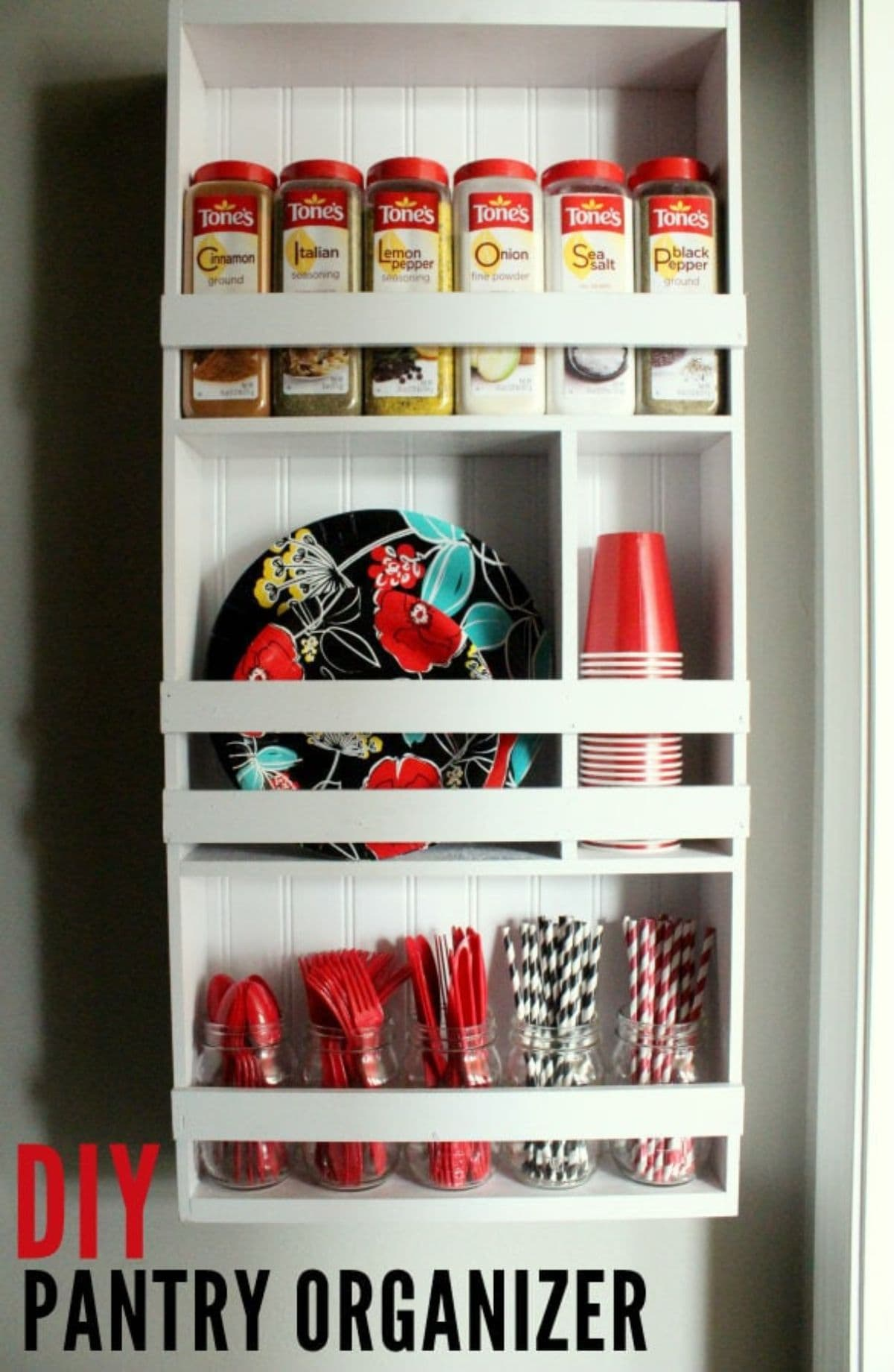 The inside of a cupboard is show, made of white wood. On the shelves are pantry items and storage goods.
