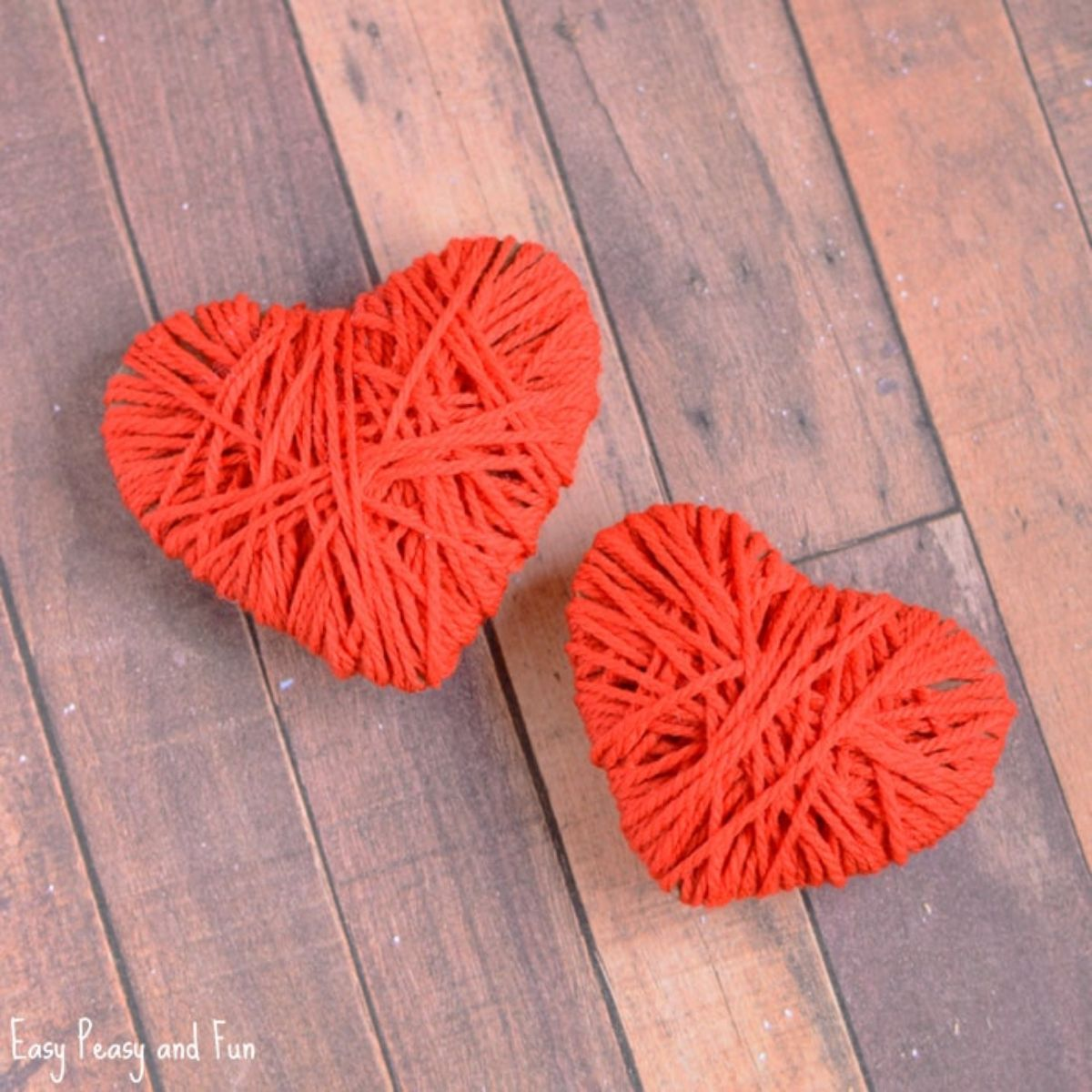 2 red yarn hearts sit on a wooden table