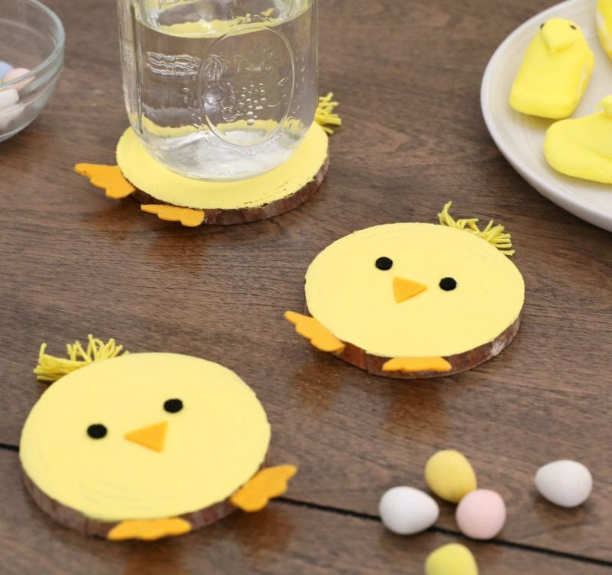 on a wooden table, 3 wooden coasters have been painted to look like yellow chicks. One of them has a mason jar sitting on it