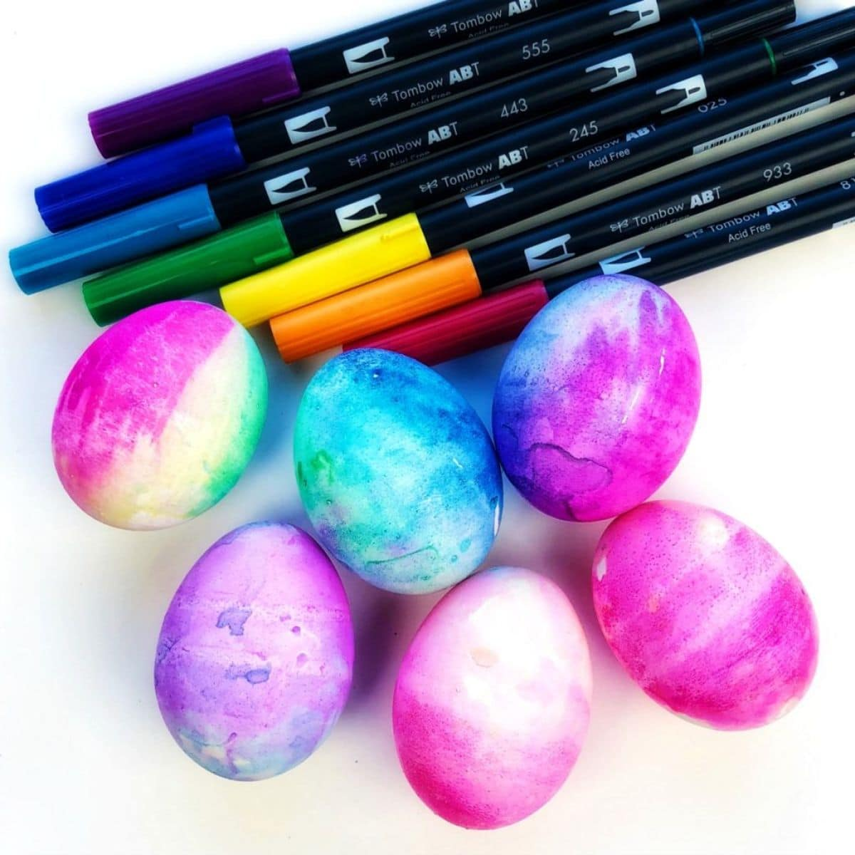a pile of brush pens sit above six decorated hard boiled eggs on a white background
