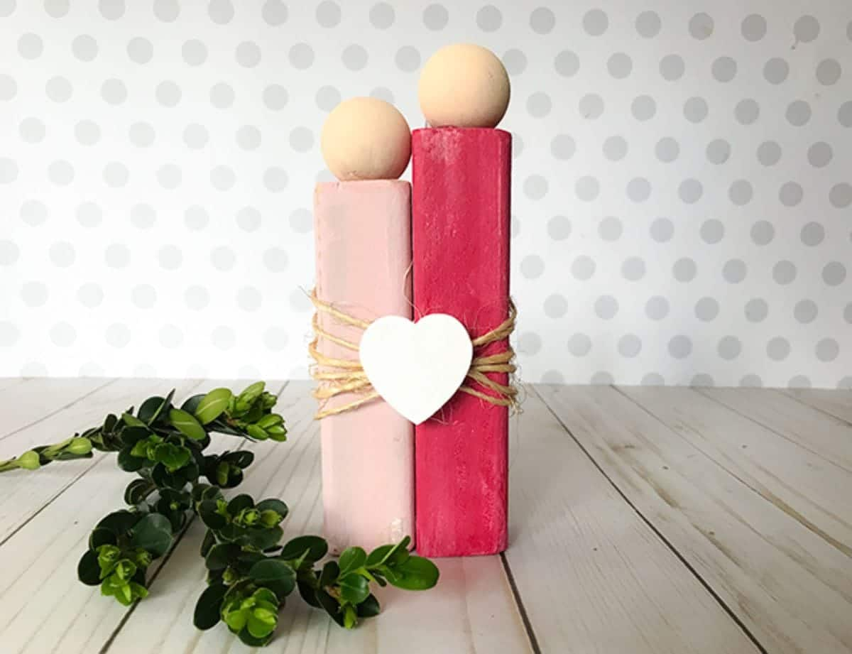 on a light wooden table, next to some green foliage is a scuplture of 2 people made of rectangular blocks of wood, one red, one pink. Wooden balls are their heads and they are tied together with twine and a white heart