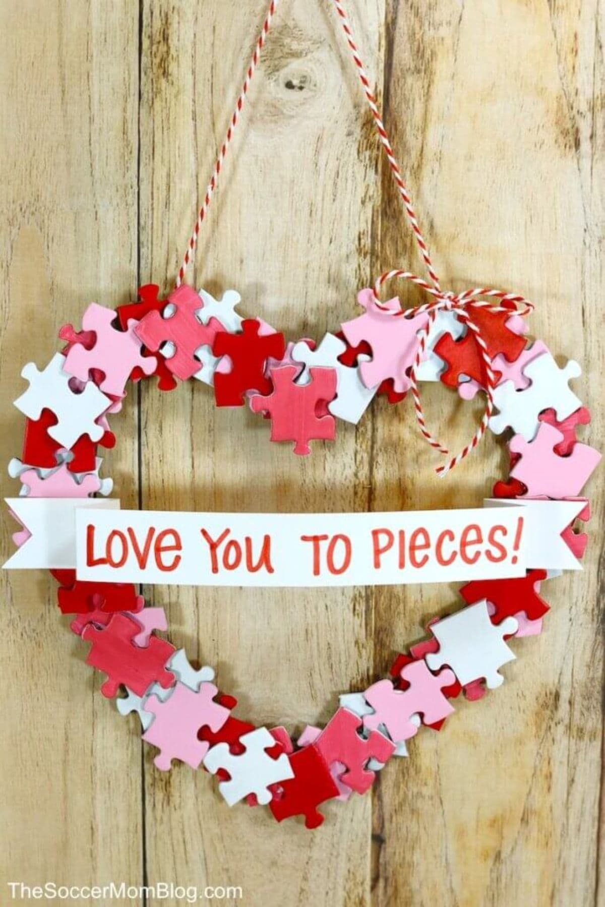 "On a wooden background is a heart shape made of red, pink and white puzzle pieces. Across the middle is a scroll shap in white with the red text ""Love you to pieces"""