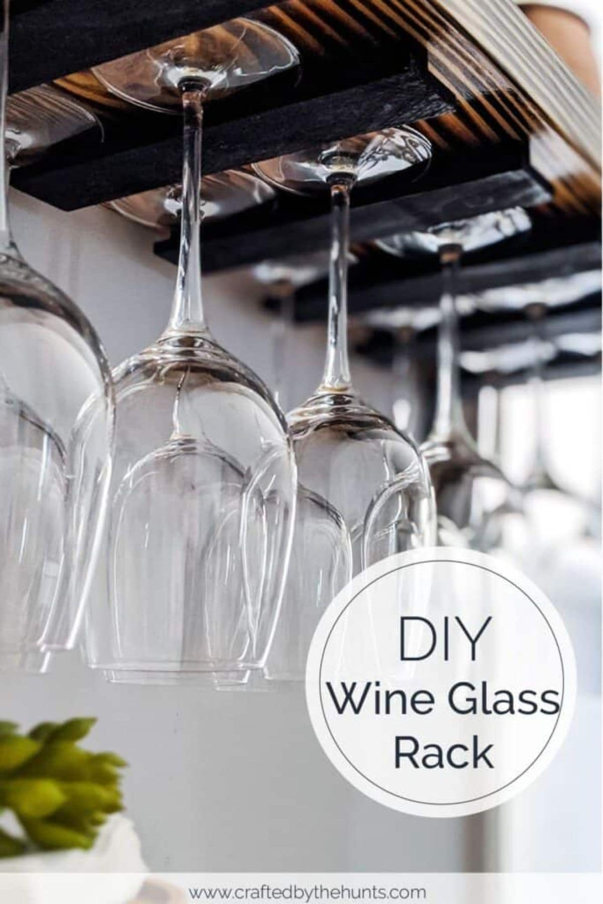 A wine glass rack made of dark wood with large win glasses hooked upside down from it