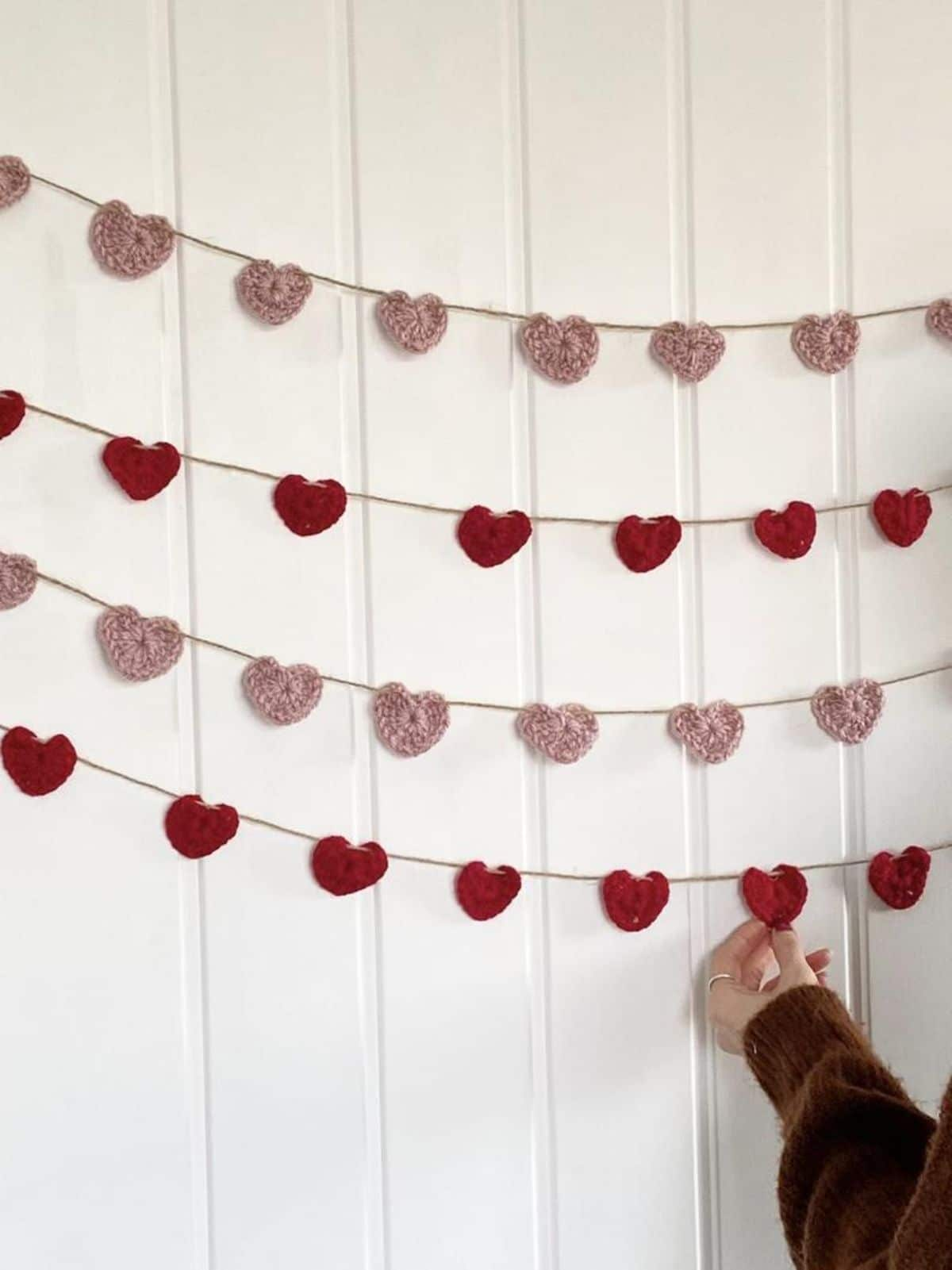 ON a white batten wall are 2 strings of red hearts and 2 strings of pink hearts