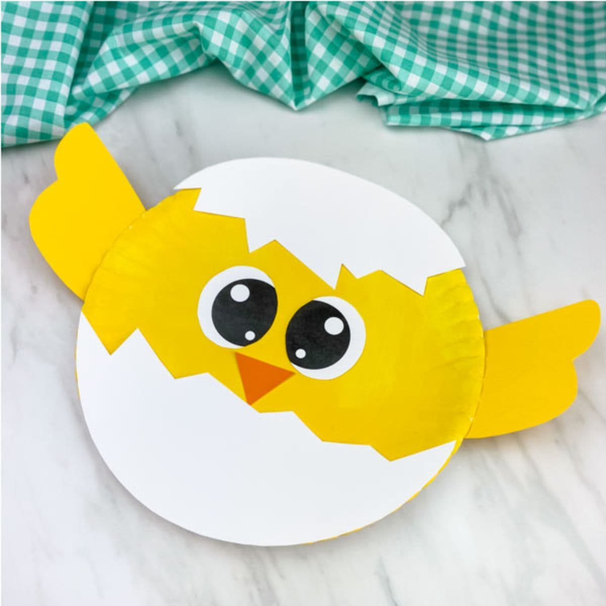On a marble surface there is a yellow and white chick made out of a paper plate.