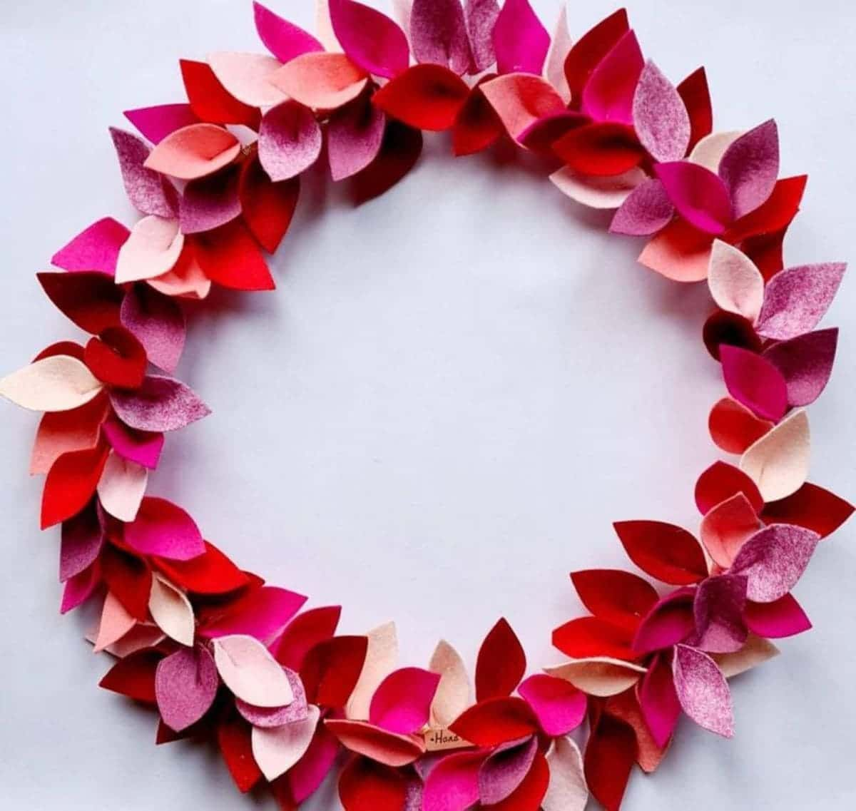 On a white background is a circular wreath made of red, pink and dark pink felt leaves