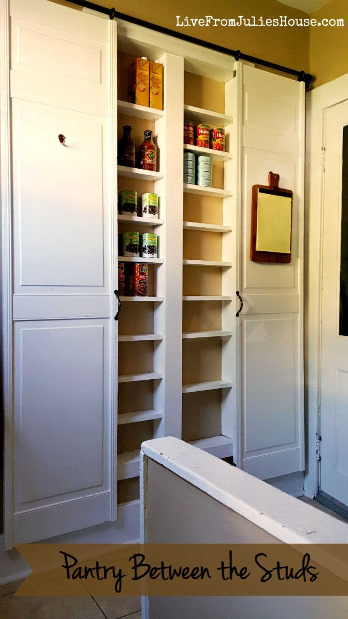 In between two white cabinets are two cut away spaces filled with shallow shelves.