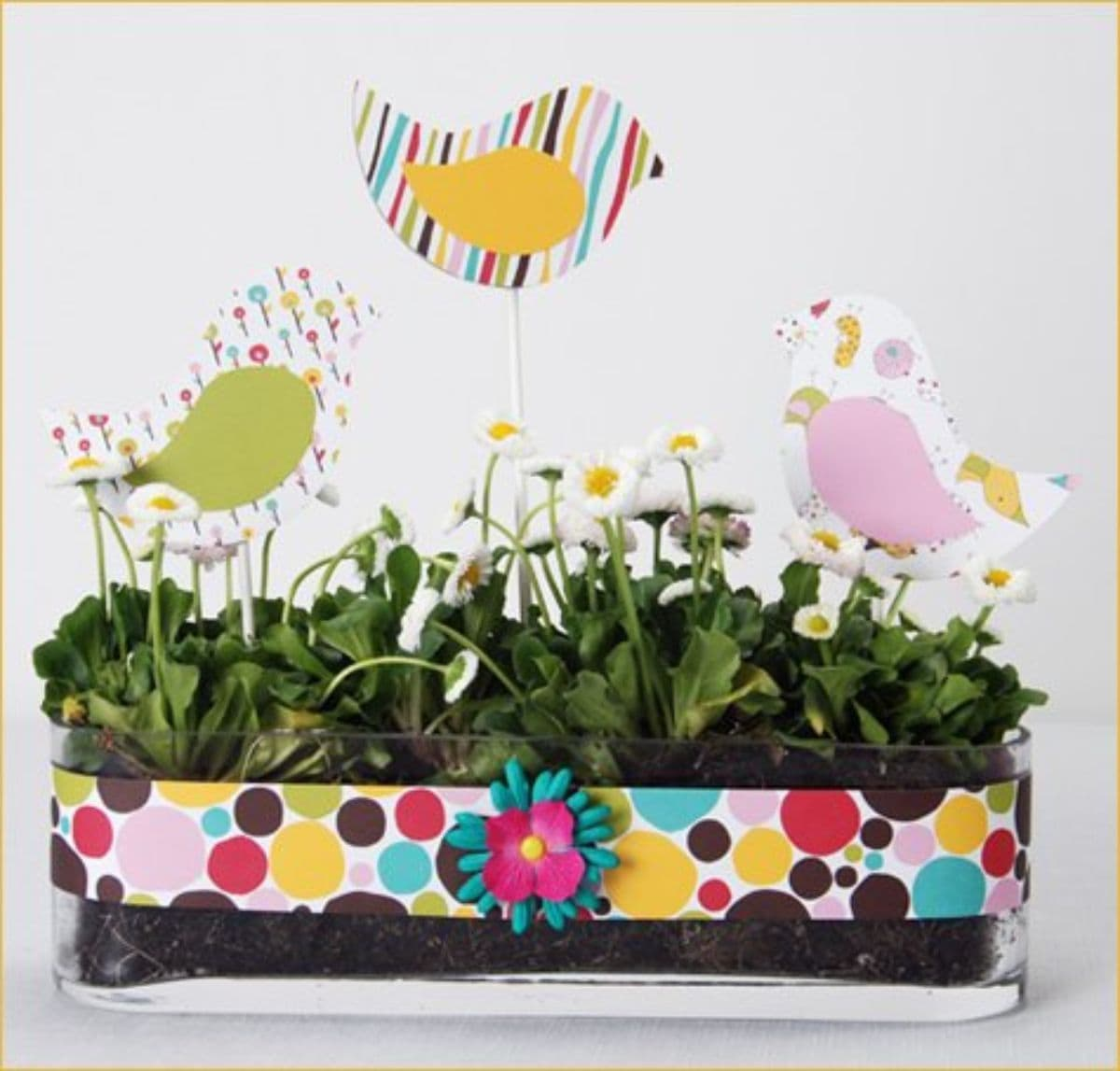A clear tub is filled with green foliage. There is a spotty ribbon wrapped aroun dit and sticking out of the top are 3 paper birds