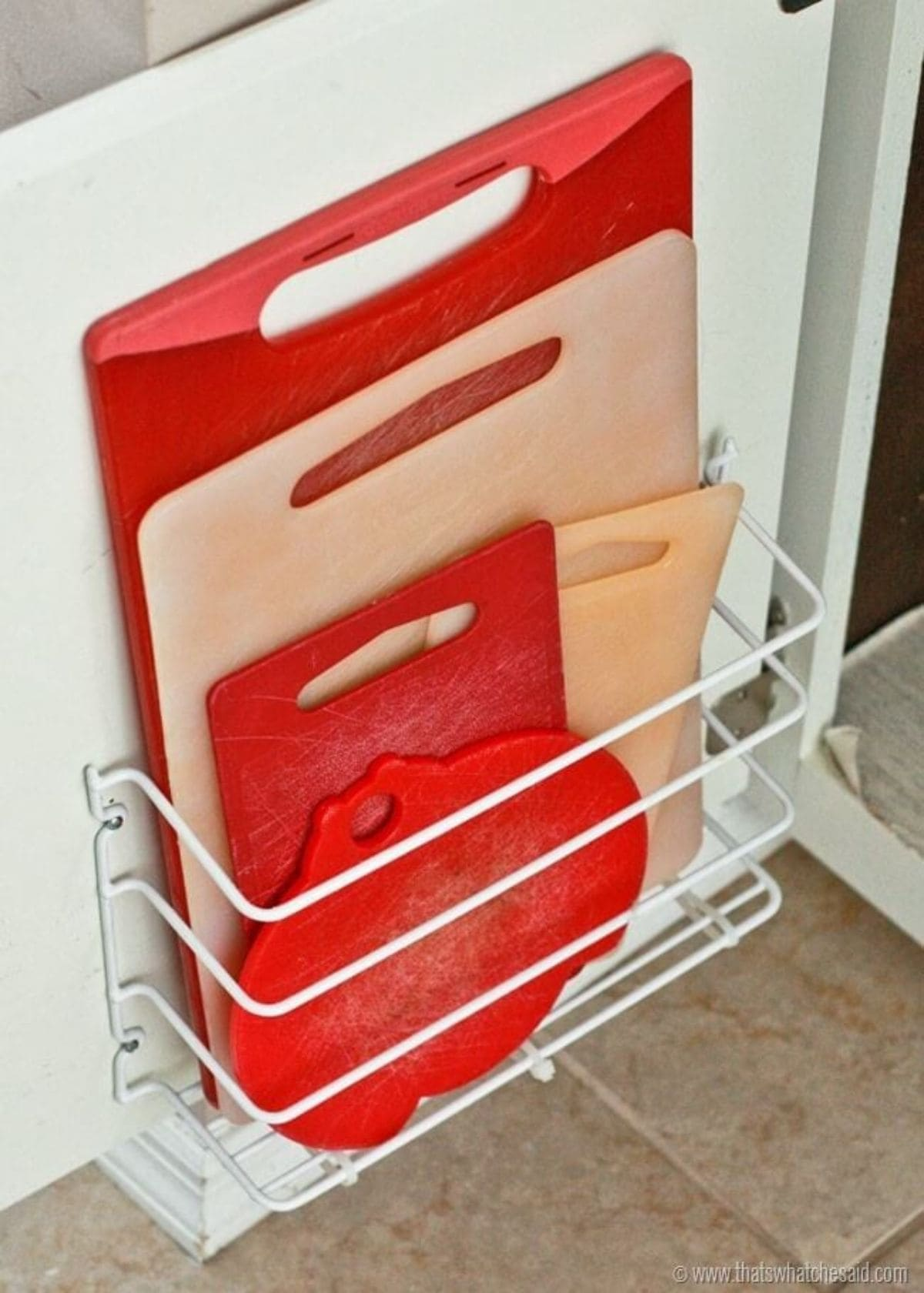 Inside the door of a cupboard a wire magazine rack has been fitted. Inside are red and white chopping boards