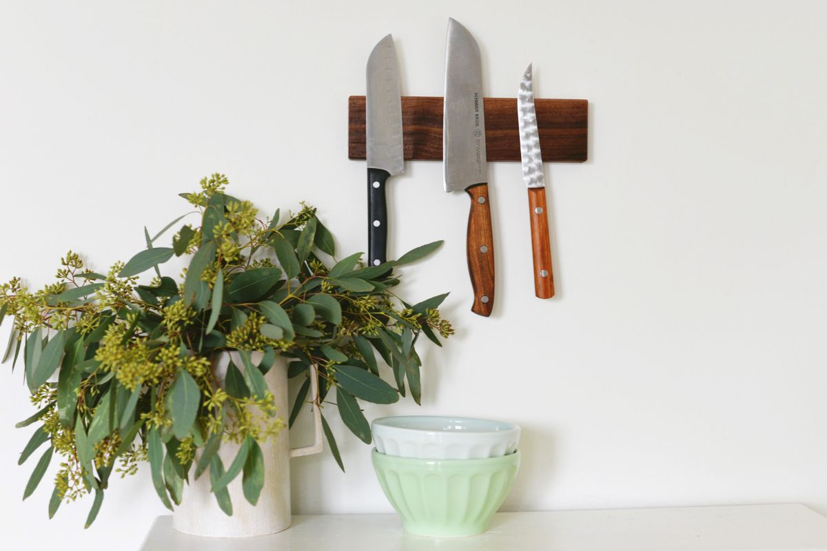 On a white wall is a wooden rectangle. Stuck to it are 3 different sized knives. In front is a potted plant in a white pot and a small bowl.