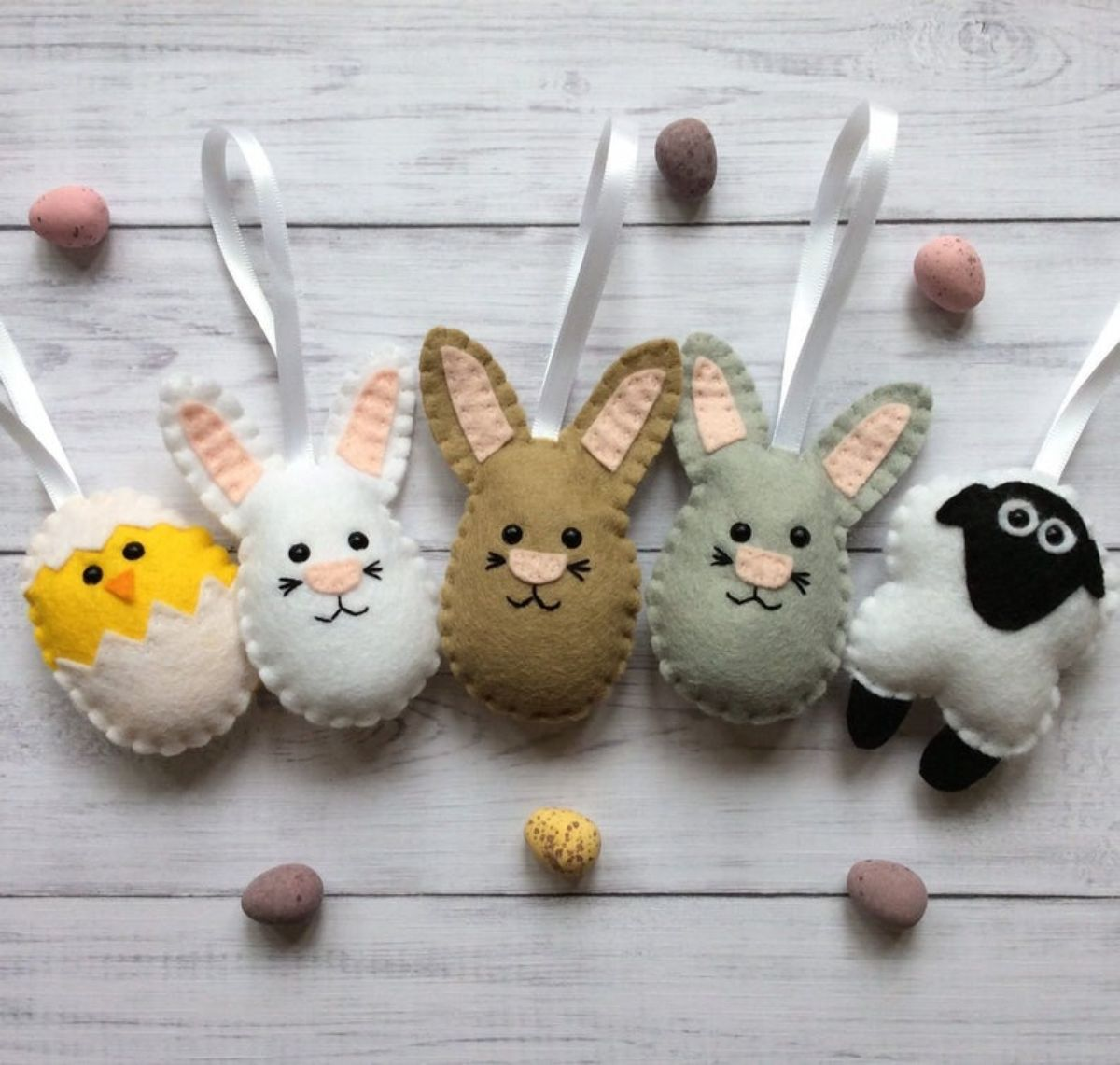 On a light wood backgrouns are a chick, mouse, brown and grey bunnies, and a sheep made out of felt