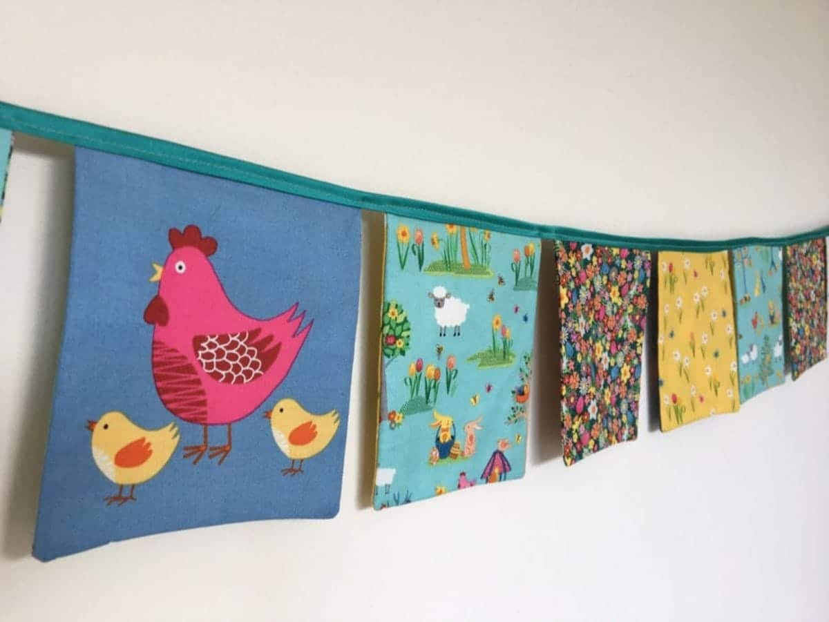 a garland of fabric squares hangs on a wall. One has a red chicken on it, others have different colored flower fabrics.
