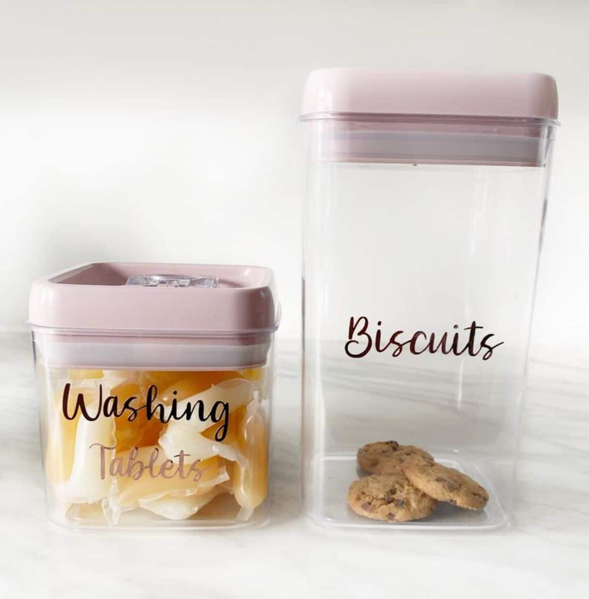 """Two glass square pots with white lids. Labelled """"washing tablets"""" and """"biscuits"""""""