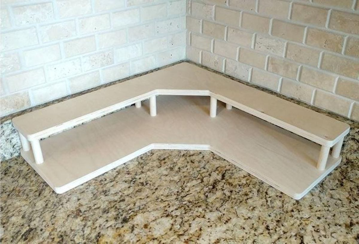 The corner of a kitchen worktop is shown. Sitting up agains tthe wall of white tiles is a two story wooden shelf
