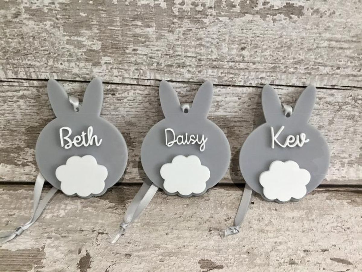 on a background of wooden planks, sit 3 grey bunnies with white tails and names on each of their backs