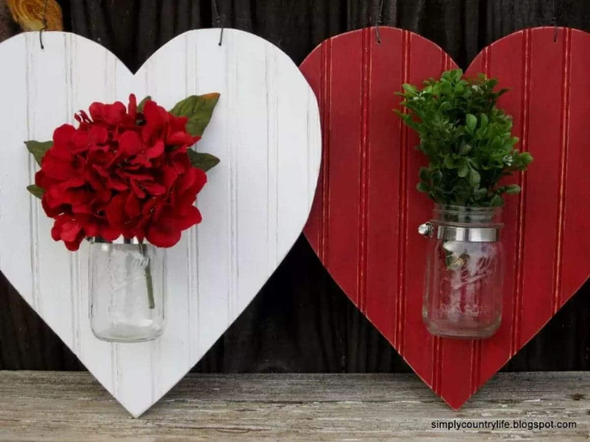 a white wooden heart is propped up next to a red wooden heart. Each heart has a glass mason jar stuck the front. inside the mason jar is a bunch of red flowers and green foliage