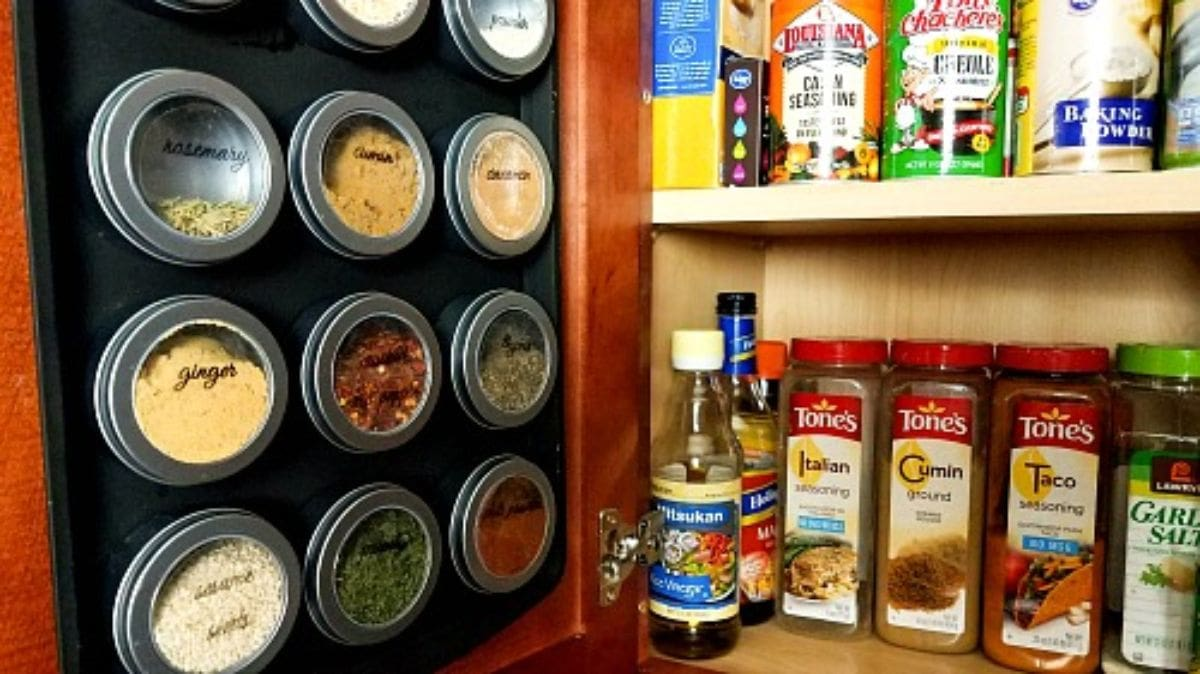 an open cupbaord, with packets and bottles on the shelves on the right hand side of the picture. The door has been painted in black paint and circular metal spice jars are stuck to it with magnets