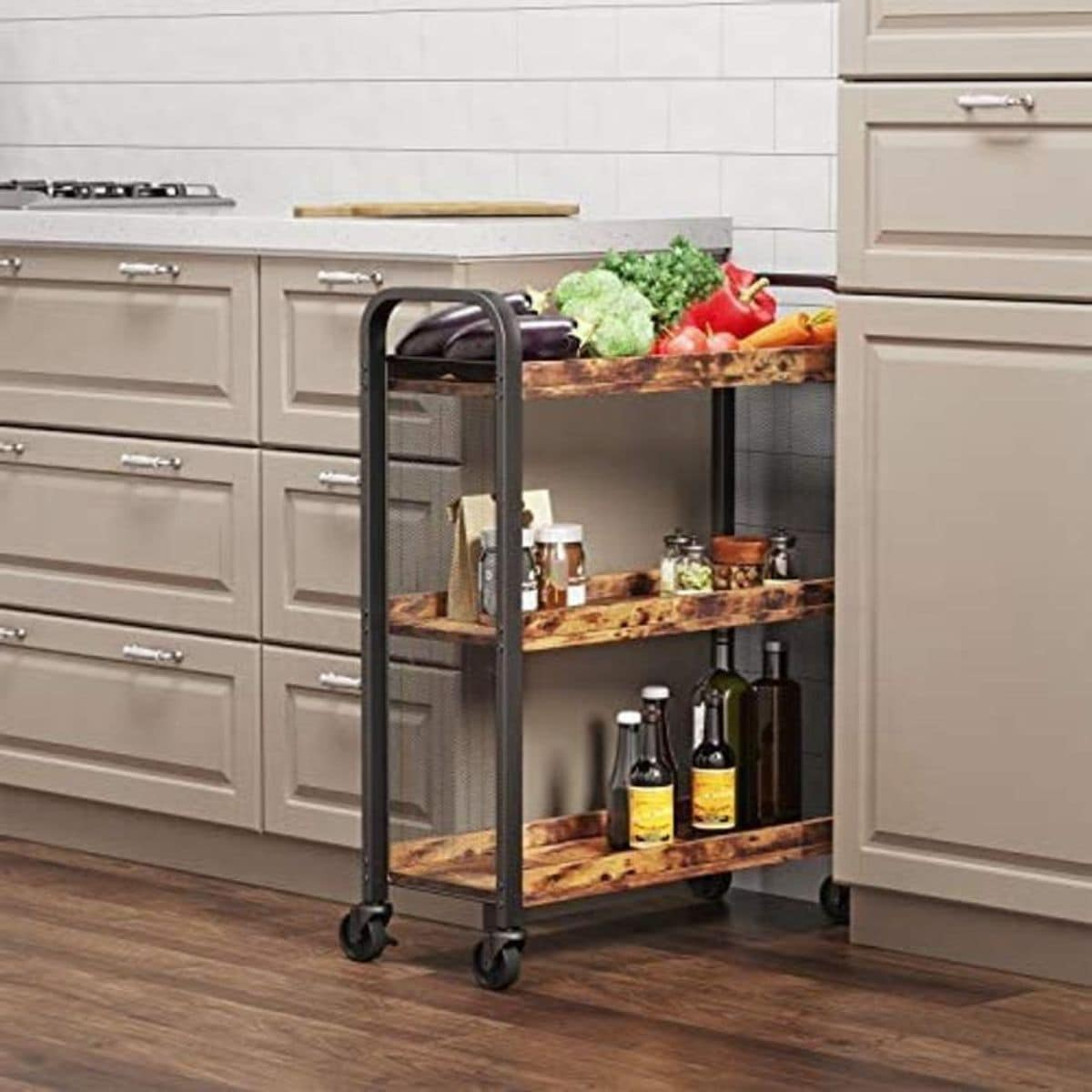 in front of a cream kitchen is a wheeled trolley with 3 tiers made of sarker metal and wooden shelves. Vegetables, condments and bottles sit on the shelves.
