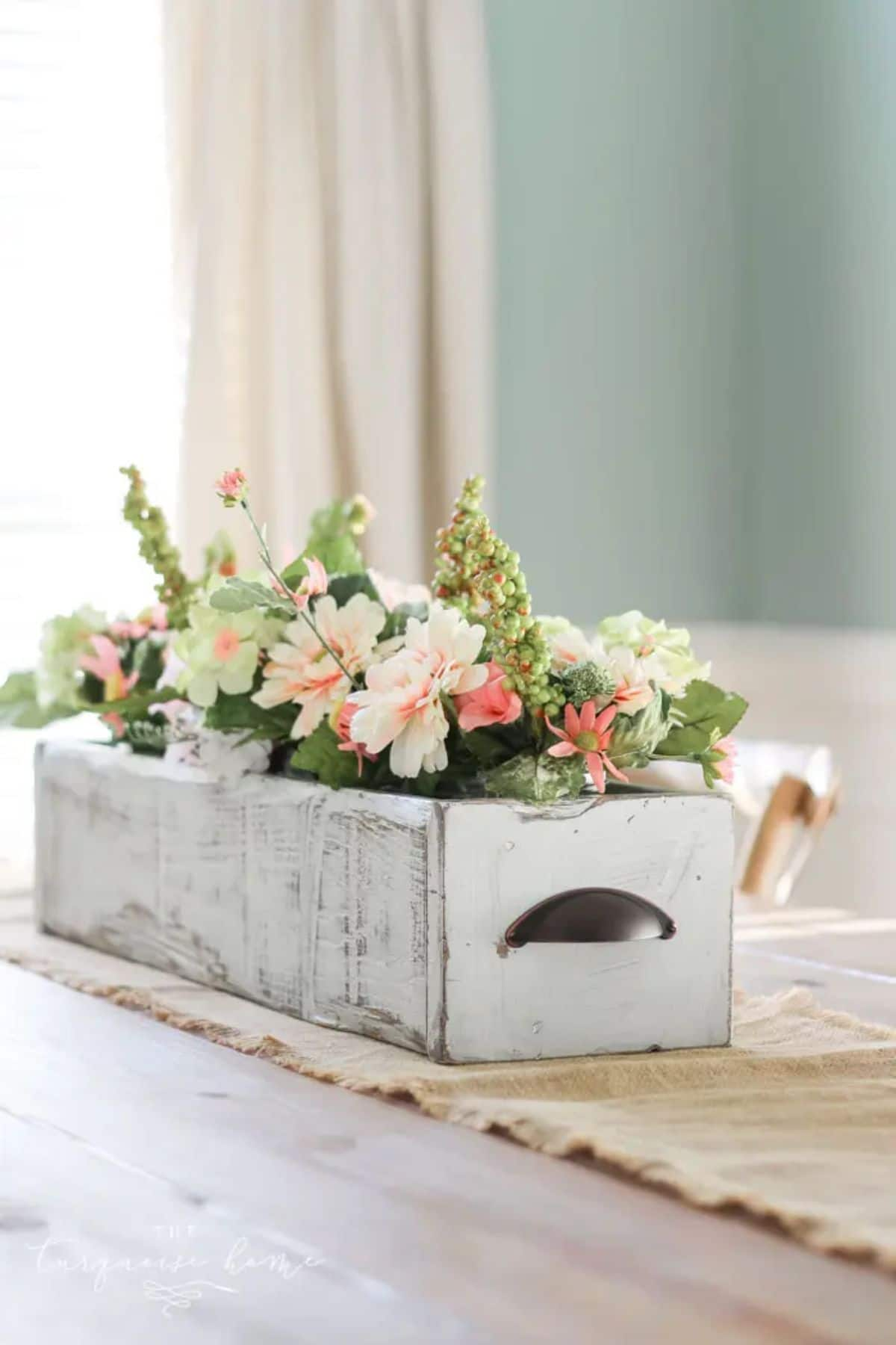 on a wooden table, sitting on top of a table runner is a shabby chic painted crate filled with pin kand white flowers