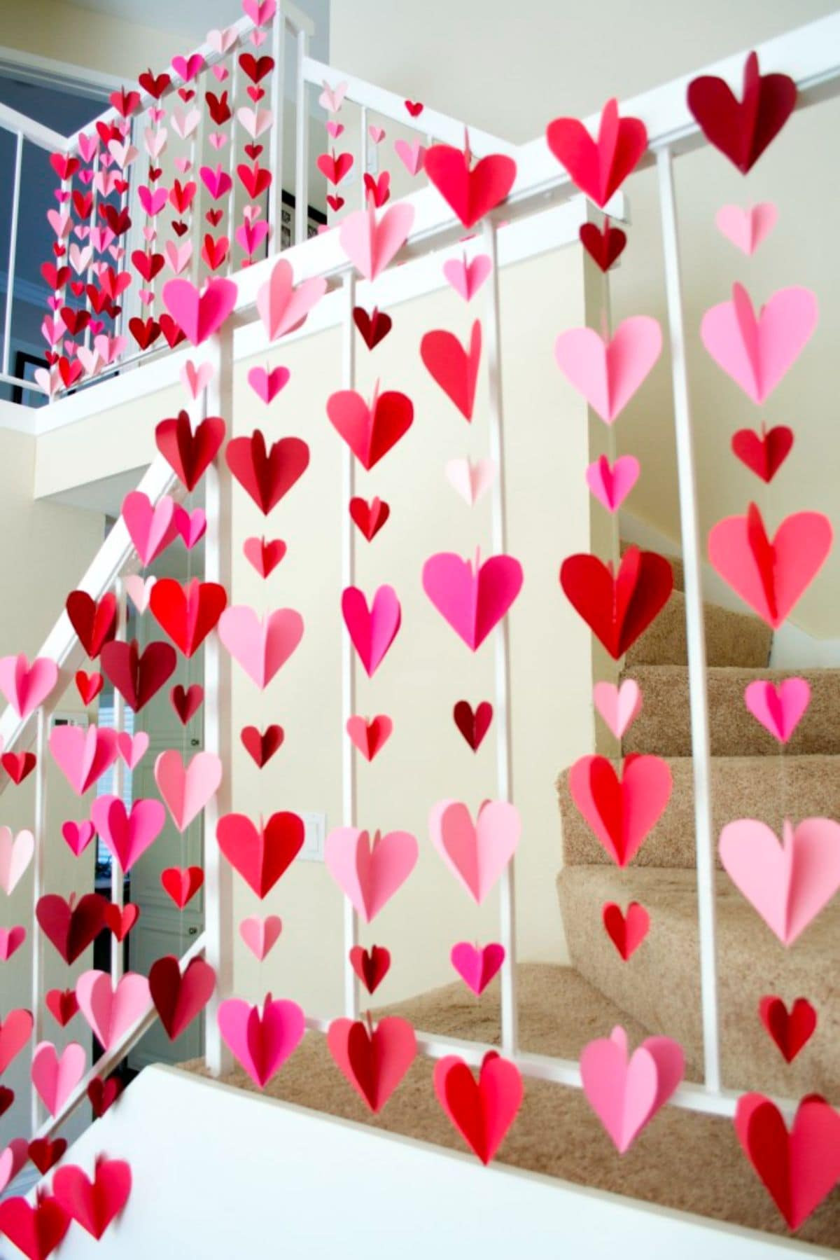 hanging from the top of a shelf are several strings with 3D paper hearts strung vertically from them