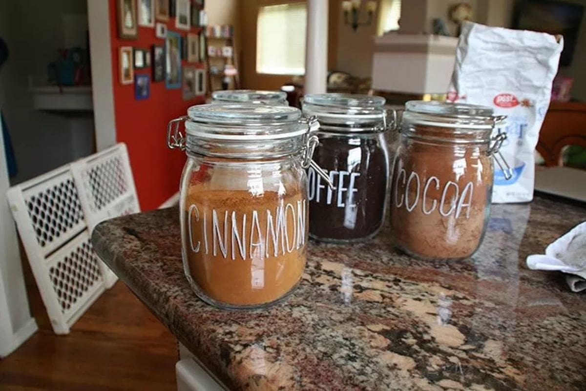 On a marble countertop sit 3 glass mason jars. They have chalk writing on them labelling their contents: Cinnamon, Coffee adn Cocoa.
