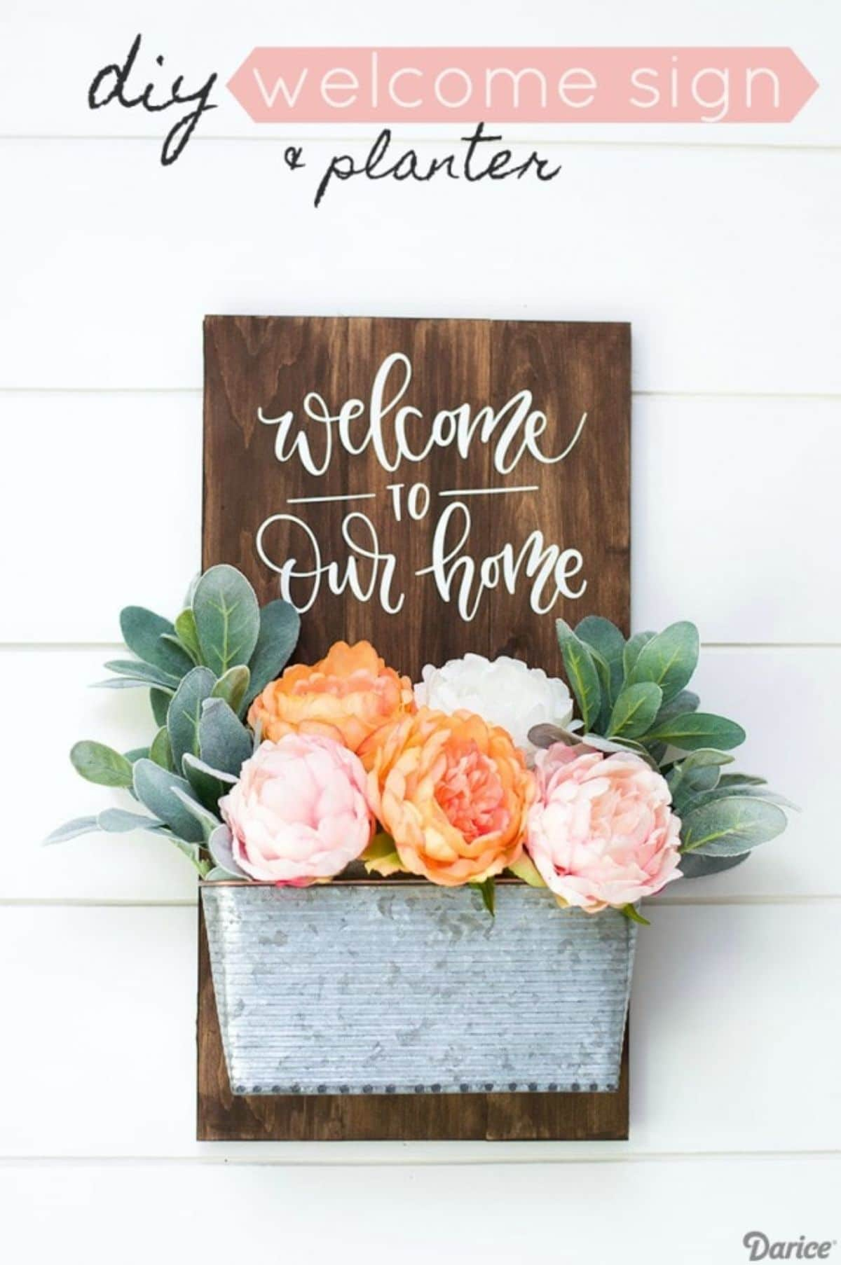 """On a white background is a dark wooden board with """"Welcome to our house"""". Stuck to the front of it is a metal tub filled with orange and pink flowers"""