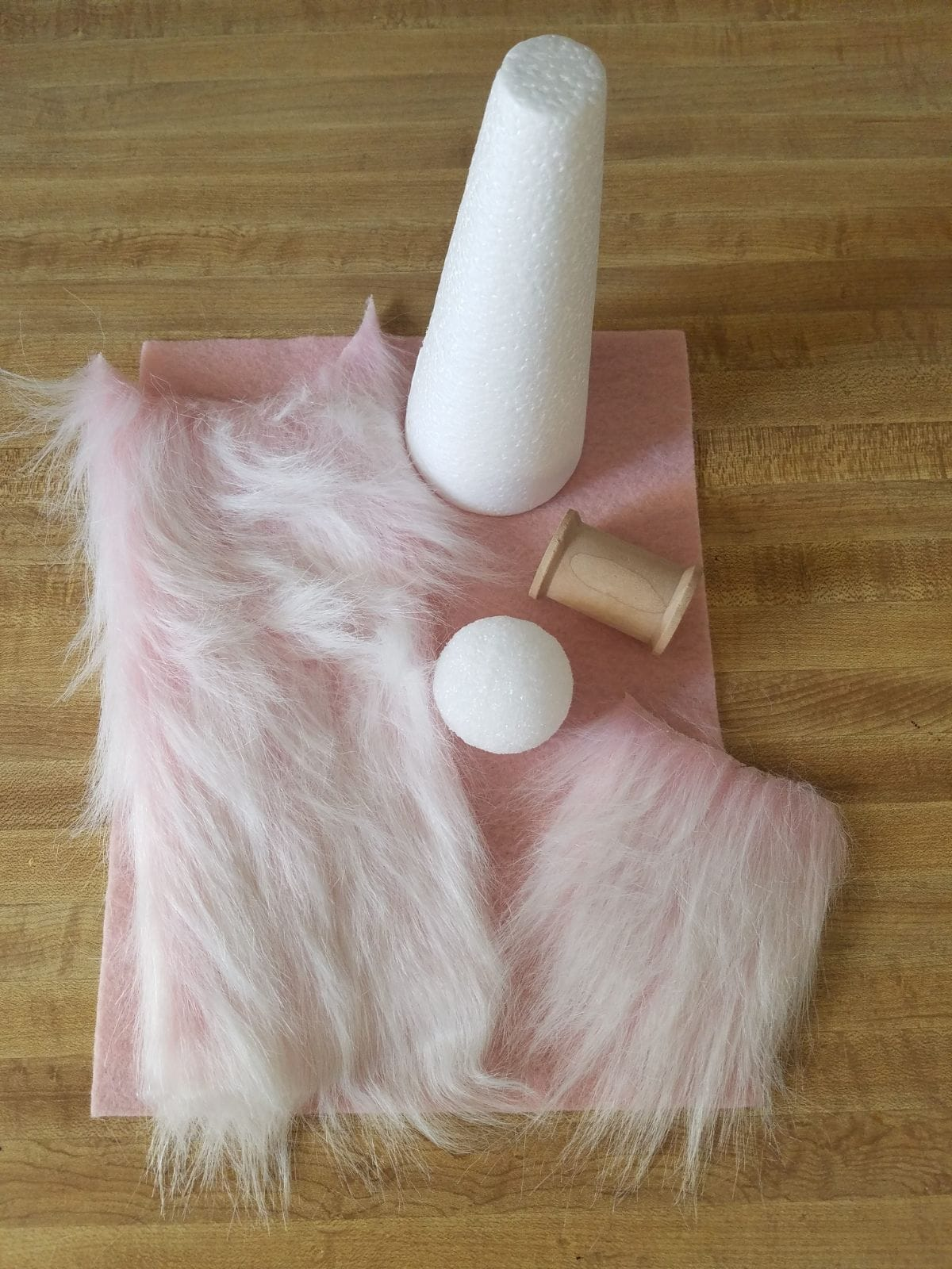 On a wooden table sits a pink ssquare of fabric. On top of the fabric are 2 pieces of faux fur, a ping pong ball, a reel of cotton and a yarn cone
