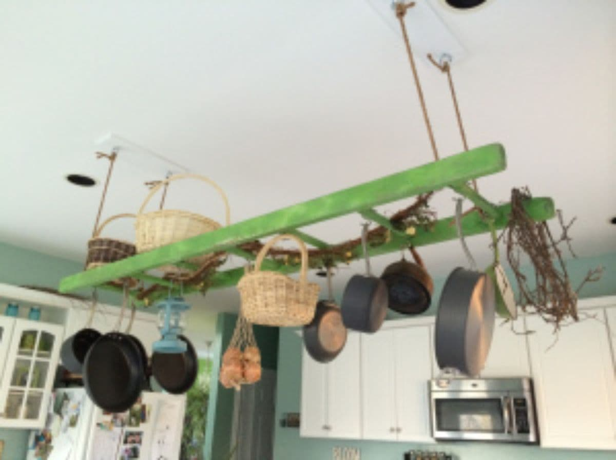 Hanging from a white ceiling with rope is a green ladder. Hanging from the ladder are several pots and pans