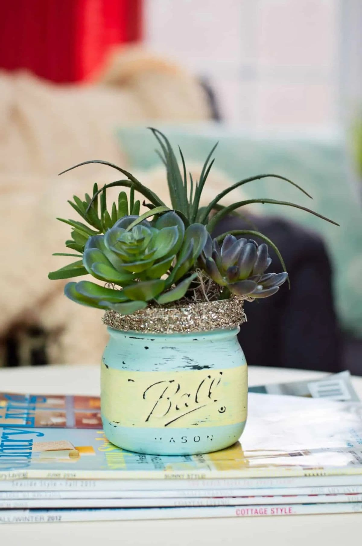 A mason jar painted in blue and green stripes sits on a table. It is filled with a succulent plant