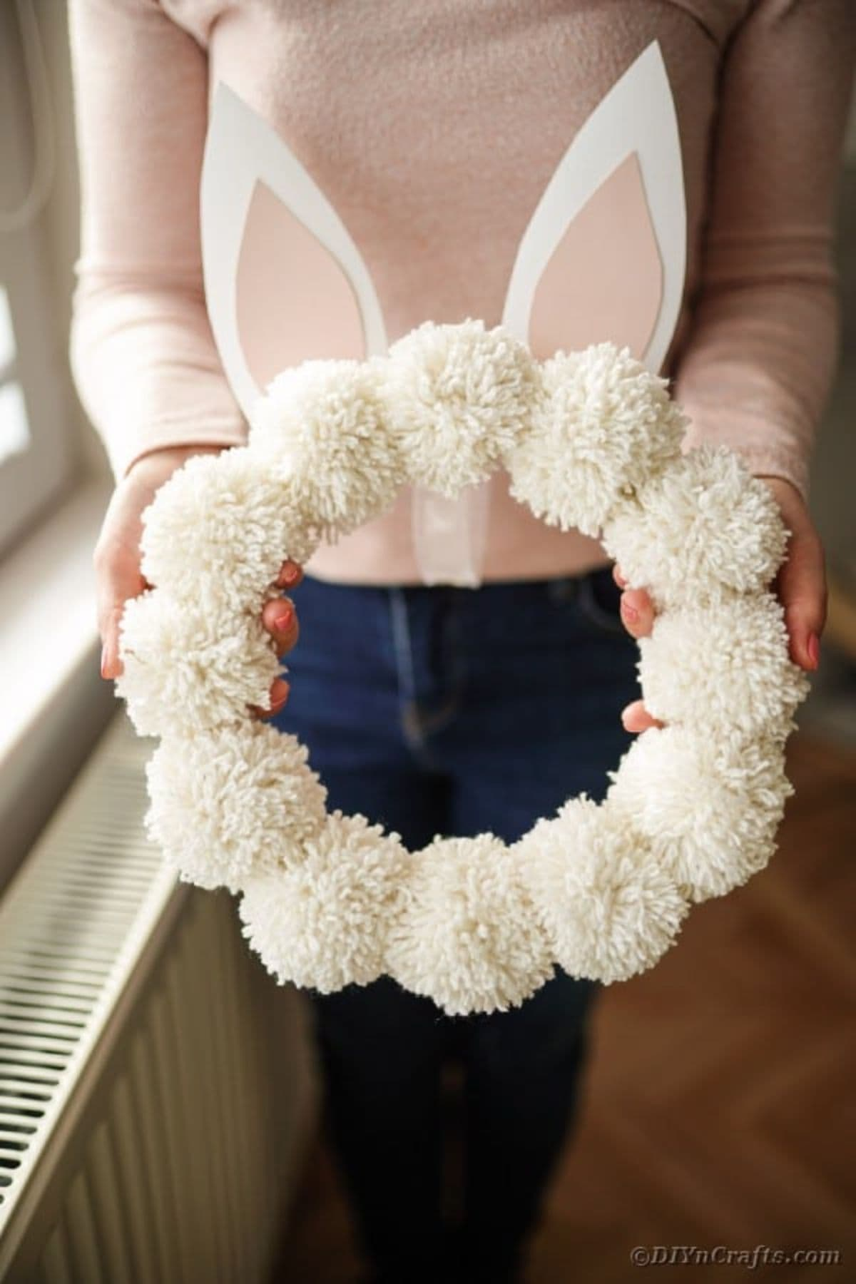 a woman in a white top and blue jeans is holding a wreath made of white pom poms with white bunny ears on the top