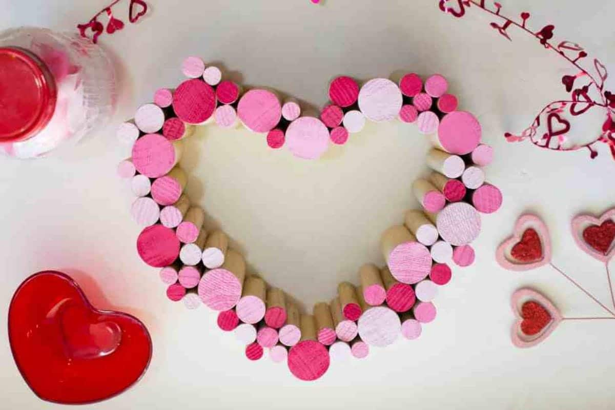 On a white background, a heart shape has been made out of dowel sections of different widths in differetn shades of pink.