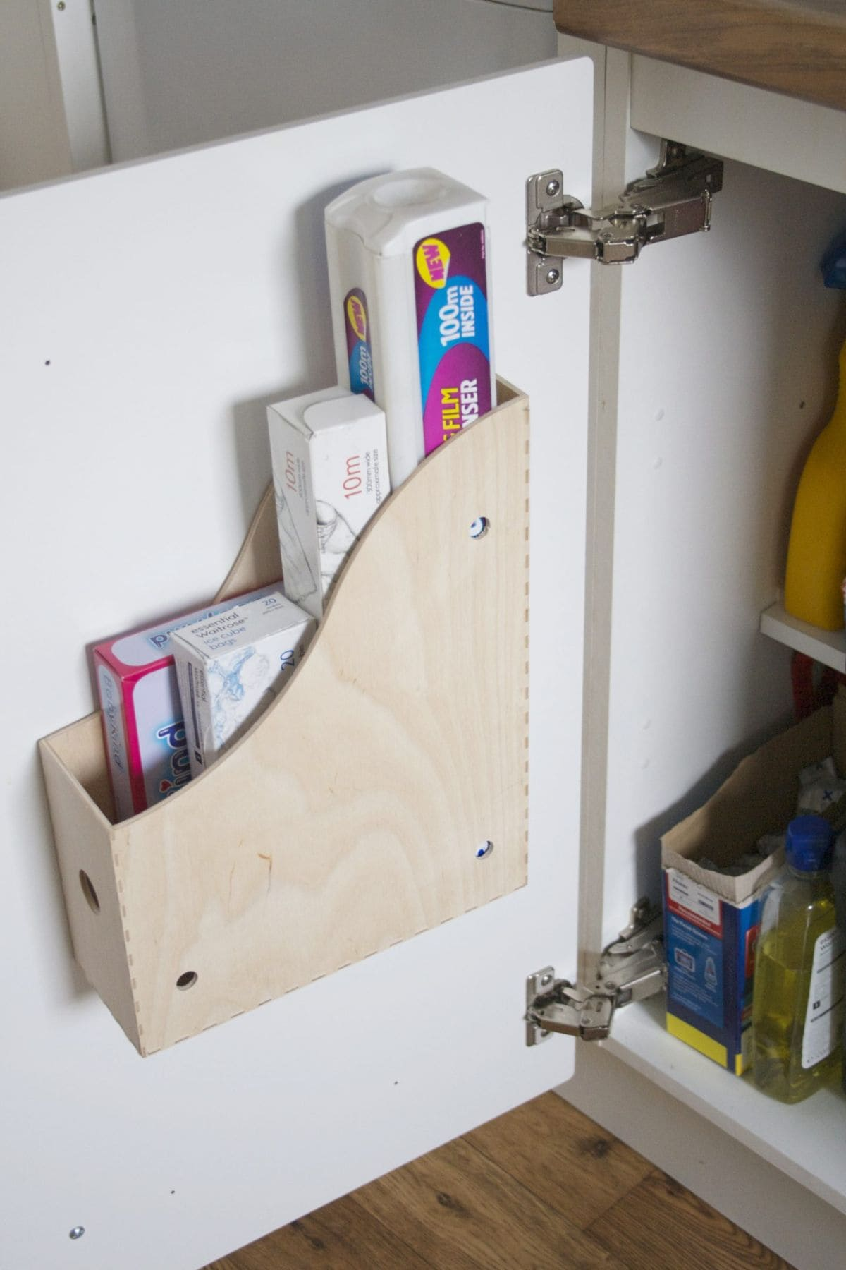 The inside of a kitchen cabinet is shown. On the door a wooden magazine rack has been fixed and rolls of cling film and foil put inside